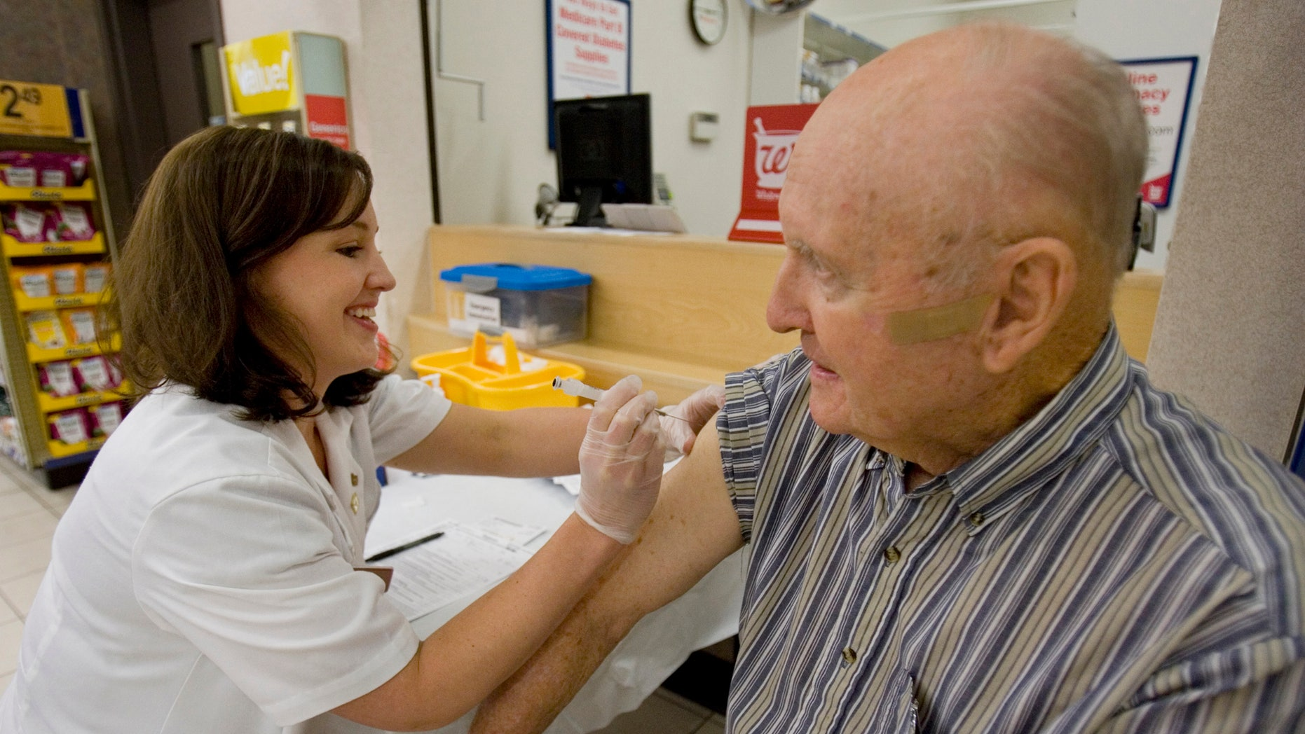 Maurice Brannon, 88 of Columbia, S.C. get his seasonal flu shot from Walgreen's pharmacy manager, Whitney Workman Tuesday, Sept. 1, 2009, in Columbia, S.C.