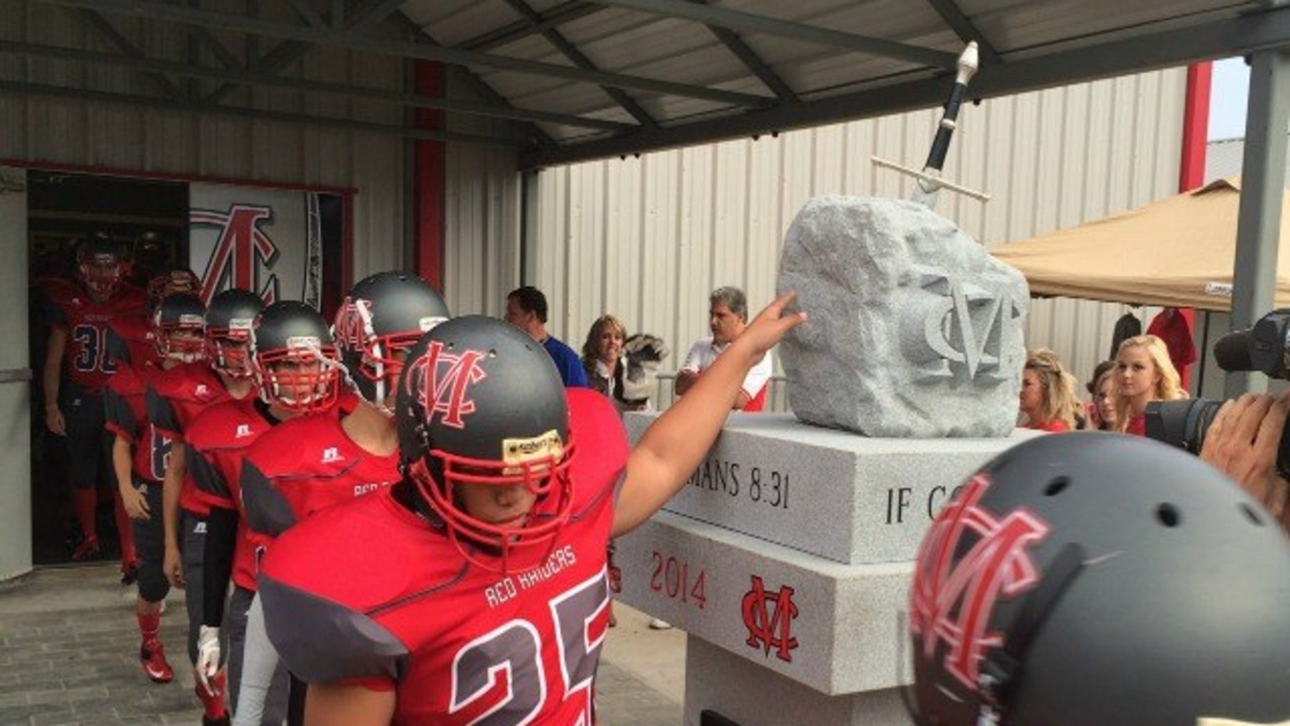 The Red Raiders of Madison County High in Danielsville, Ga., touch a granite statue on way to the field that is drawing the ire of groups that say it violates the separation of church and state.