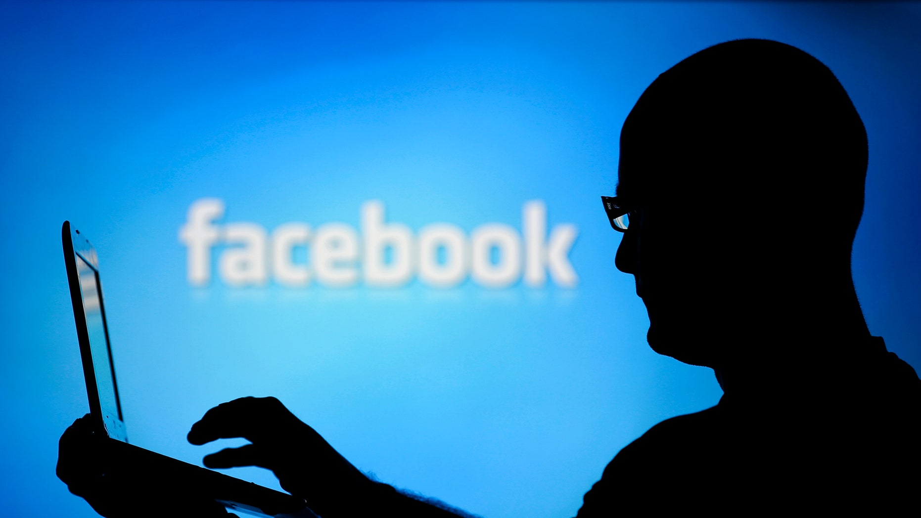 A man is silhouetted against a video screen with an Facebook logo as he poses with an Dell laptop in this photo illustration taken in the central Bosnian town of Zenica, August 14, 2013. REUTERS/Dado Ruvic (BOSNIA AND HERZEGOVINA - Tags: BUSINESS TELECOMS) - RTX12L6I