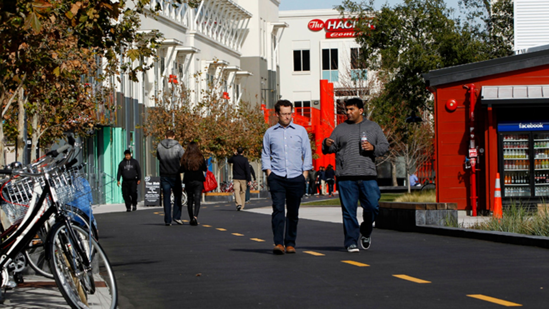 FILE: Employees walk along a walking and bicycle path at the Facebook headquarters in Menlo Park. The Internet giant said it would pay the salary of a police officer in the area.