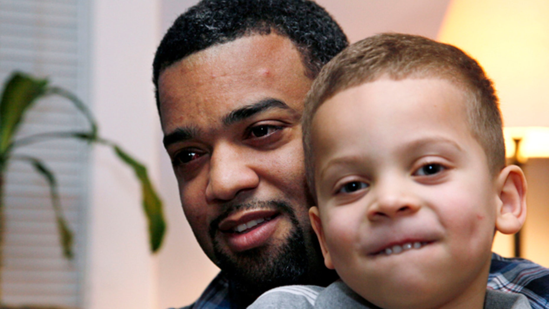 Damon Brown sits with his son Julian, 5, at their home in Seattle.