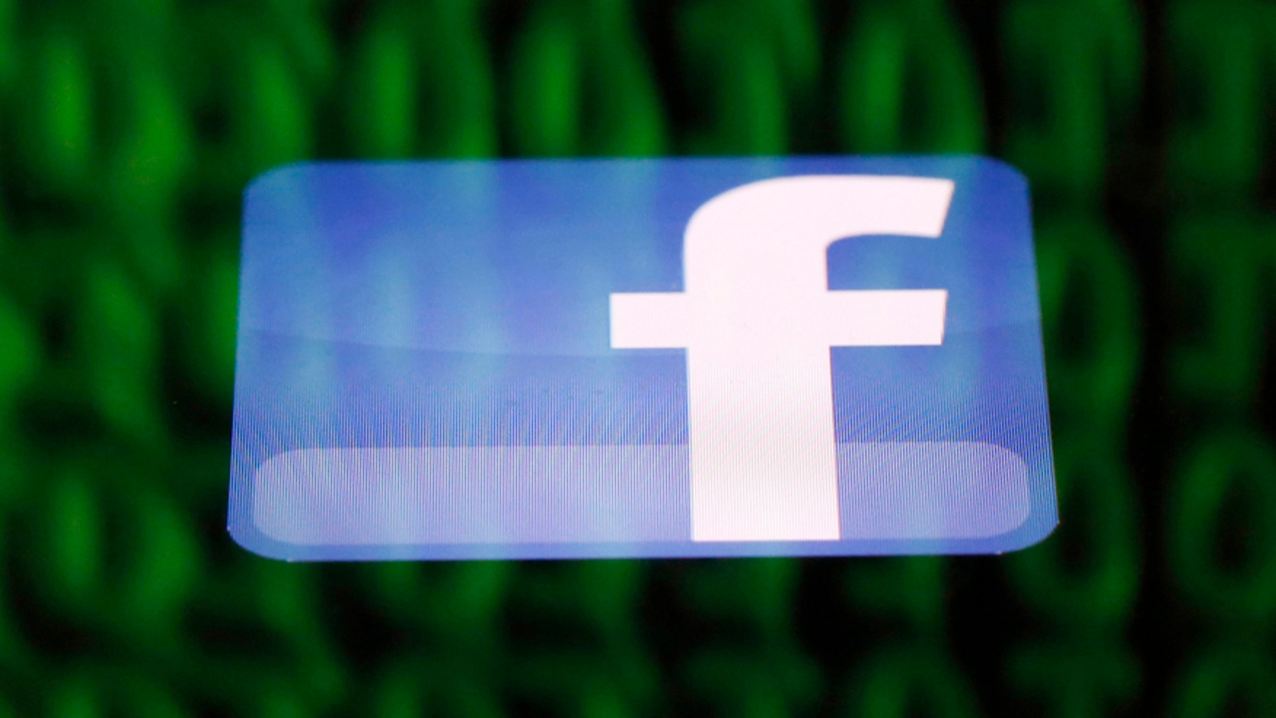 A Facebook logo on an Ipad is reflected among source code on the LCD screen of a computer, in this photo illustration taken in Sarajevo June 18, 2014.  Ireland's High Court on Wednesday asked the European Court of Justice (ECJ) to review a European Union-U.S. data protection agreement in light of allegations that Facebook shared data from EU users with the U.S. National Security Agency.   REUTERS/Dado Ruvic  (BOSNIA AND HERZEGOVINA - Tags: CRIME LAW BUSINESS POLITICS) - RTR3UH34