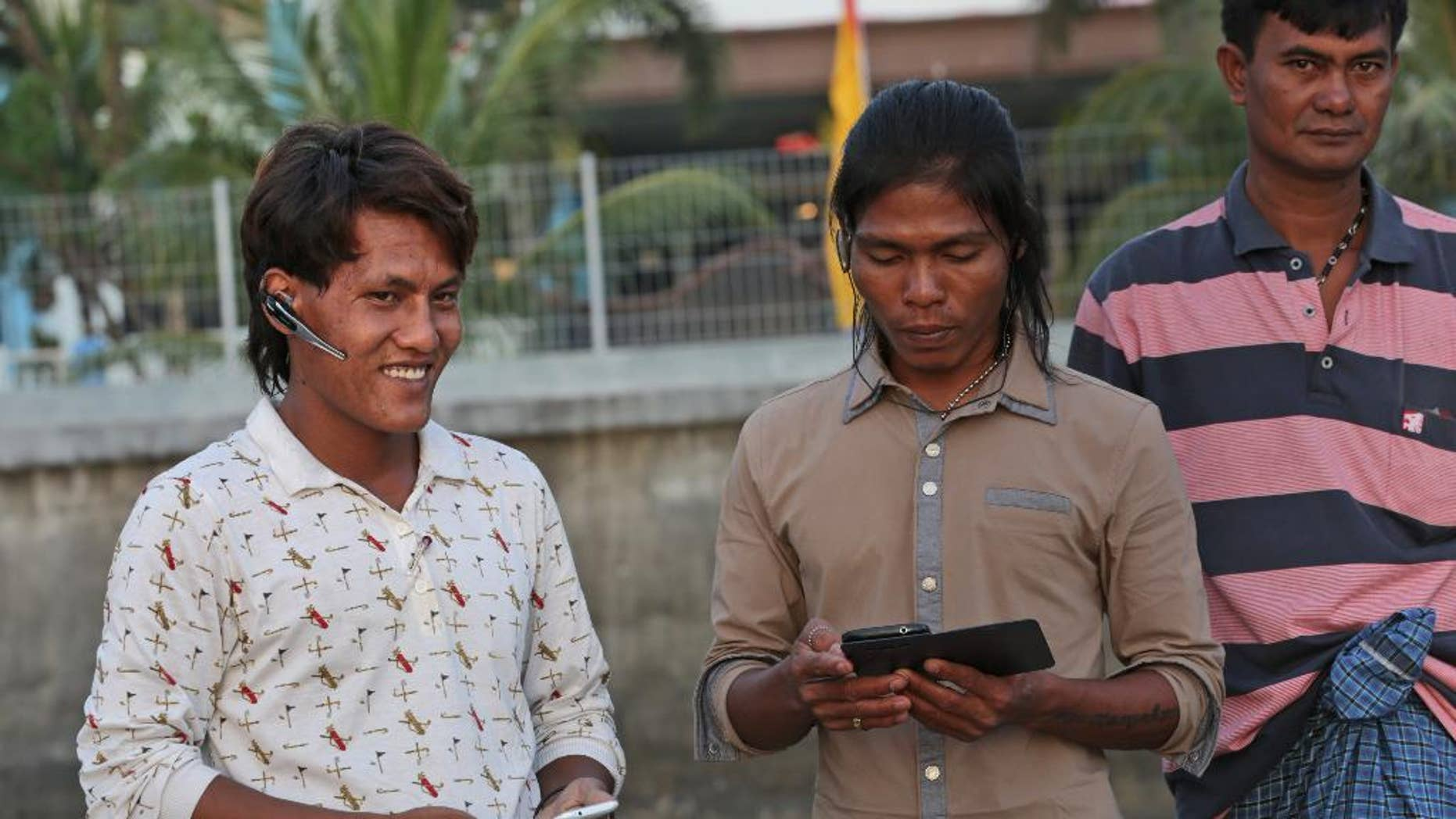 In this Sept. 9, 2015 photo, Burmese fisherman Myo Aung, left, chats with his friends outside their temporary shelter in Ambon, Maluku province, Indonesia. Myo Aung took a fishing job that he thought would keep him close to home in southern Myanmar, but he ended up thousands of miles away with no chance of return for five years. The 25-year-old is among more than 2,000 fishermen rescued this year from forced labor under brutal conditions, mainly in remote Indonesian islands, following reporting by The Associated Press and subsequent investigation by Indonesian authorities. Last week he was on Ambon island, awaiting his return home. (AP Photo/Achmad Ibrahim)