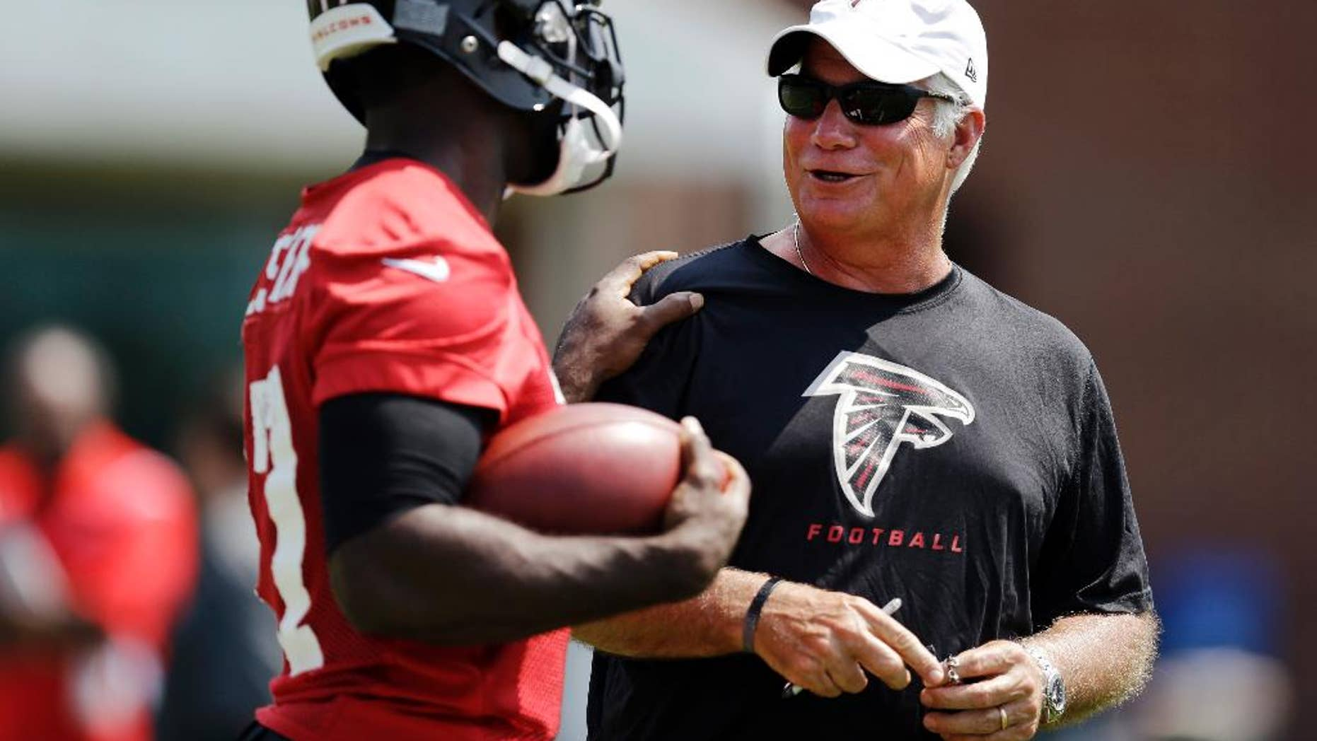 FILE - In this June 17, 2014, file photo, Atlanta Falcons head coach Mike Smith, right, talks with Devin Hester during NFL football minicamp  in Flowery Branch, Ga. (AP Photo/David Goldman, File)