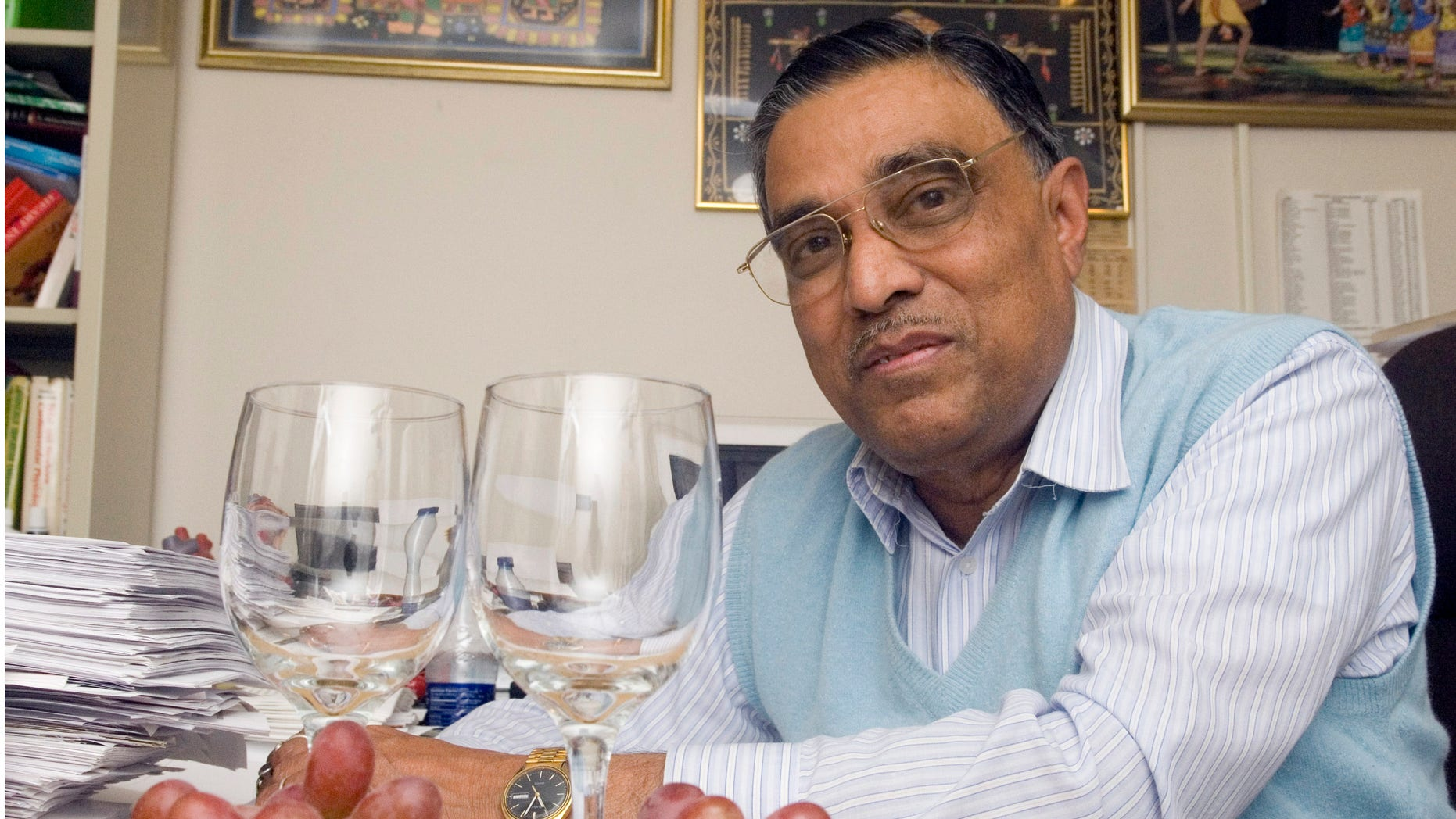 This 2006 photo shows Dipak Das with grapes and wine glasses at his office at the UConn Health Center in Farmington, Conn.