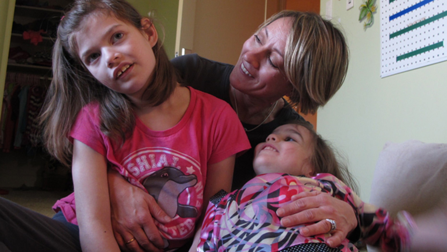Feb. 27, 2015: Alexis Carey, left, 10, sits with her mother Clare Carey, center, and her sister Alanis Carey, right, 5, in Boise, Idaho. (AP)