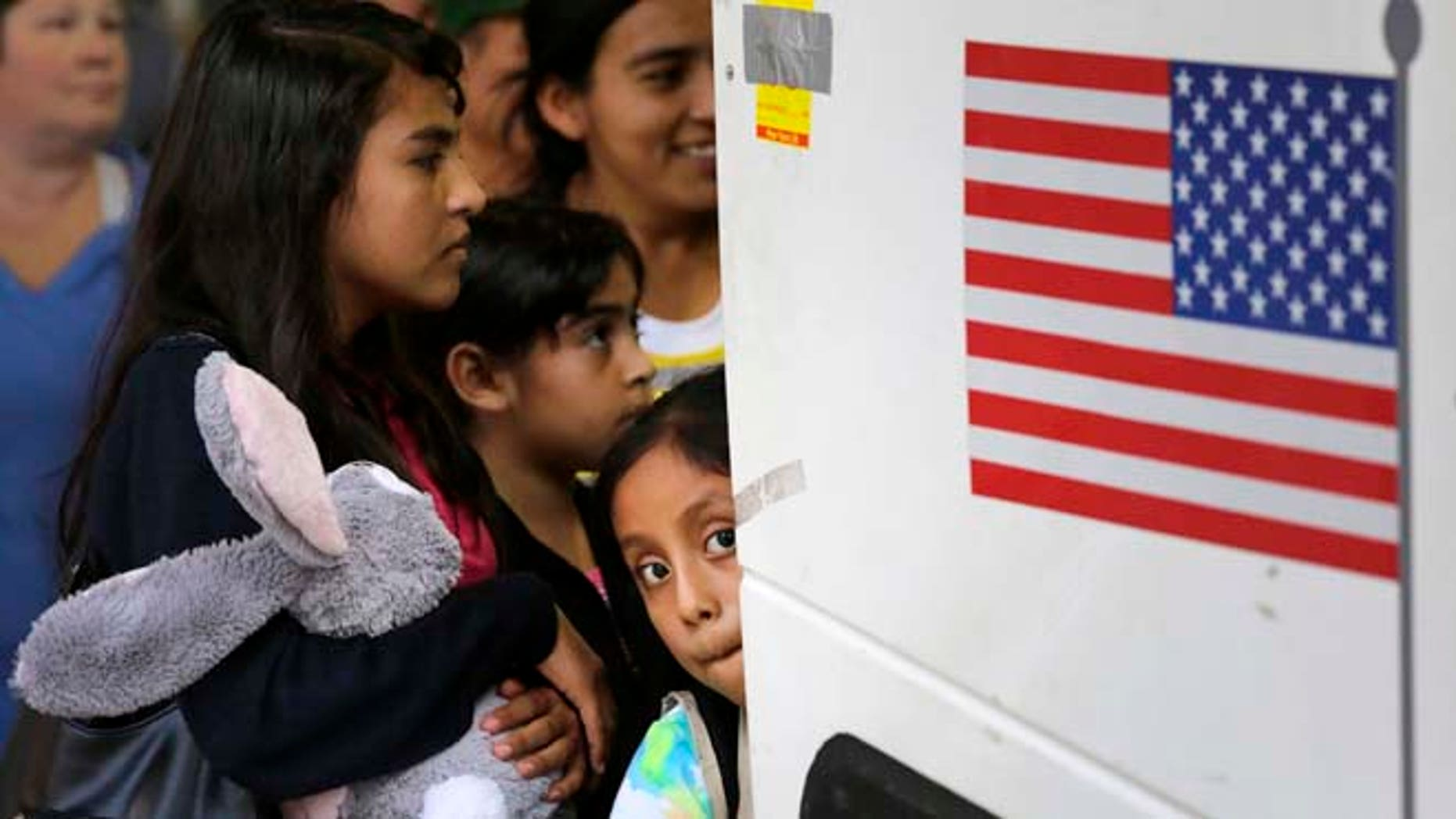 In this Tuesday, July 7, 2015, photo immigrants from El Salvador and Guatemala who entered the country illegally board a bus after they were released from a family detention center in San Antonio. Women and children are being released from immigrant detention centers faster on bond, with many mothers assigned ankle-monitoring bracelets in lieu of paying. (AP Photo/Eric Gay)