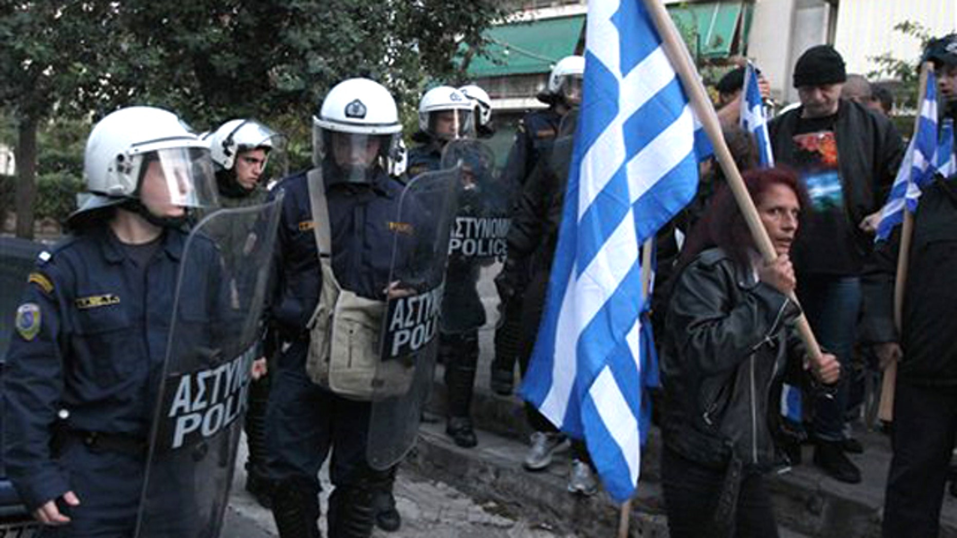 In this image taken Tuesday, Nov. 16, 2010 riot police look on a residents protest against Muslim immigrants holding outdoor prayers nearby.