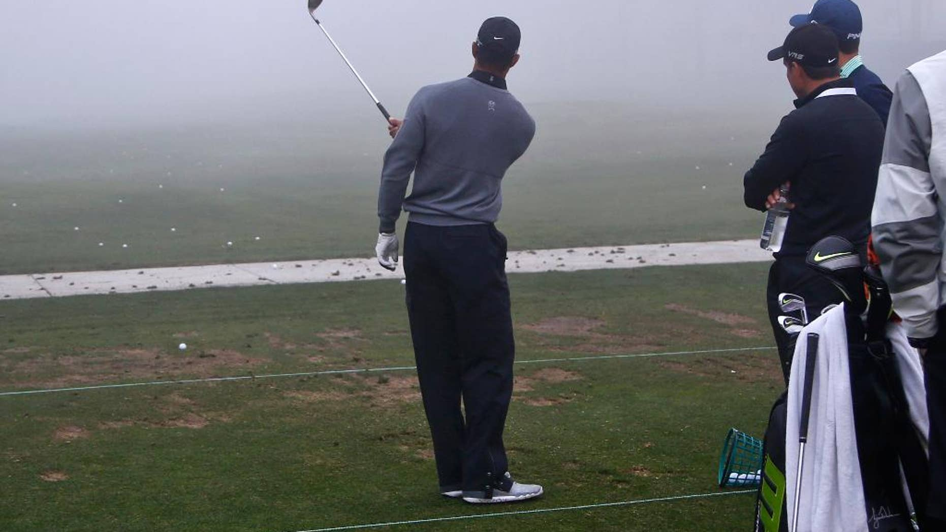 Tiger Woods hits one-handed pitch shots as his coach Chris Como, right, watches during a fog delay prior to the pro-am at the Framers Insurance Open golf tournament at Torrey Pines, Wednesday, Feb. 4, 2015, in San Diego. (AP Photo/Lenny Ignelzi)