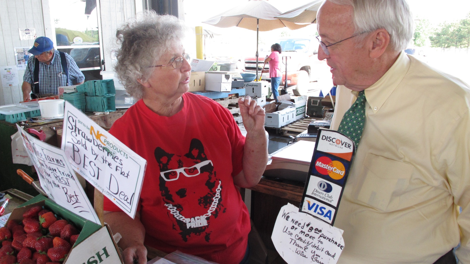 May 8, 2012: Kevin Concannon, U.S. undersecretary of agriculture, chats with vendor Helen Wise at the State Farmers Market in Raleigh, N.C.