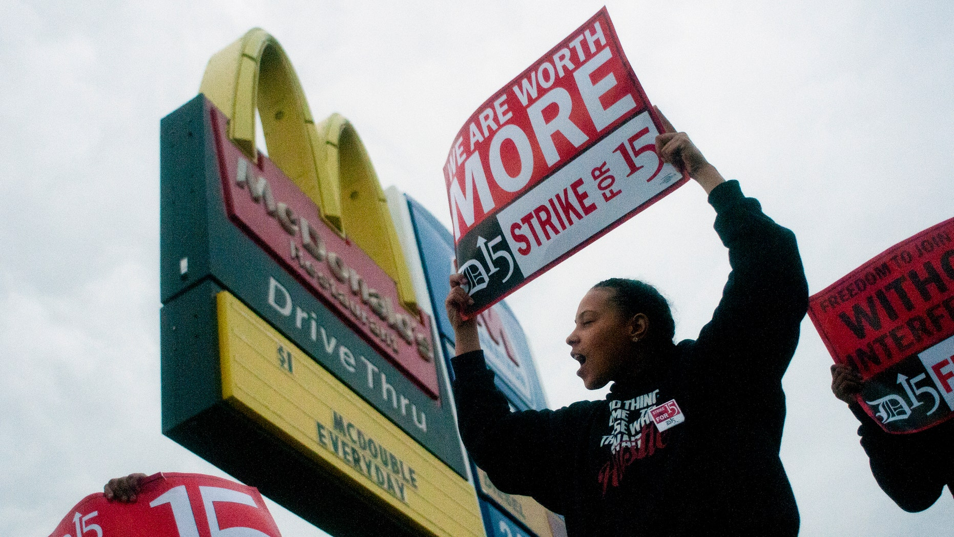 Fast-food worker Michelle Osborn, 23, of Flint, Mich. shouts out chants as she and a few dozen others strike outside of a McDonald's restaurant on Wednesday, July 31, 2013 in Flint. A few thousand fast-food workers in seven cities took to the streets demanding better pay, the right to unionize and a more than doubling of the federal minimum hourly wage from $7.25 to $15. (AP Photo/The Flint Journal, Jake May)
