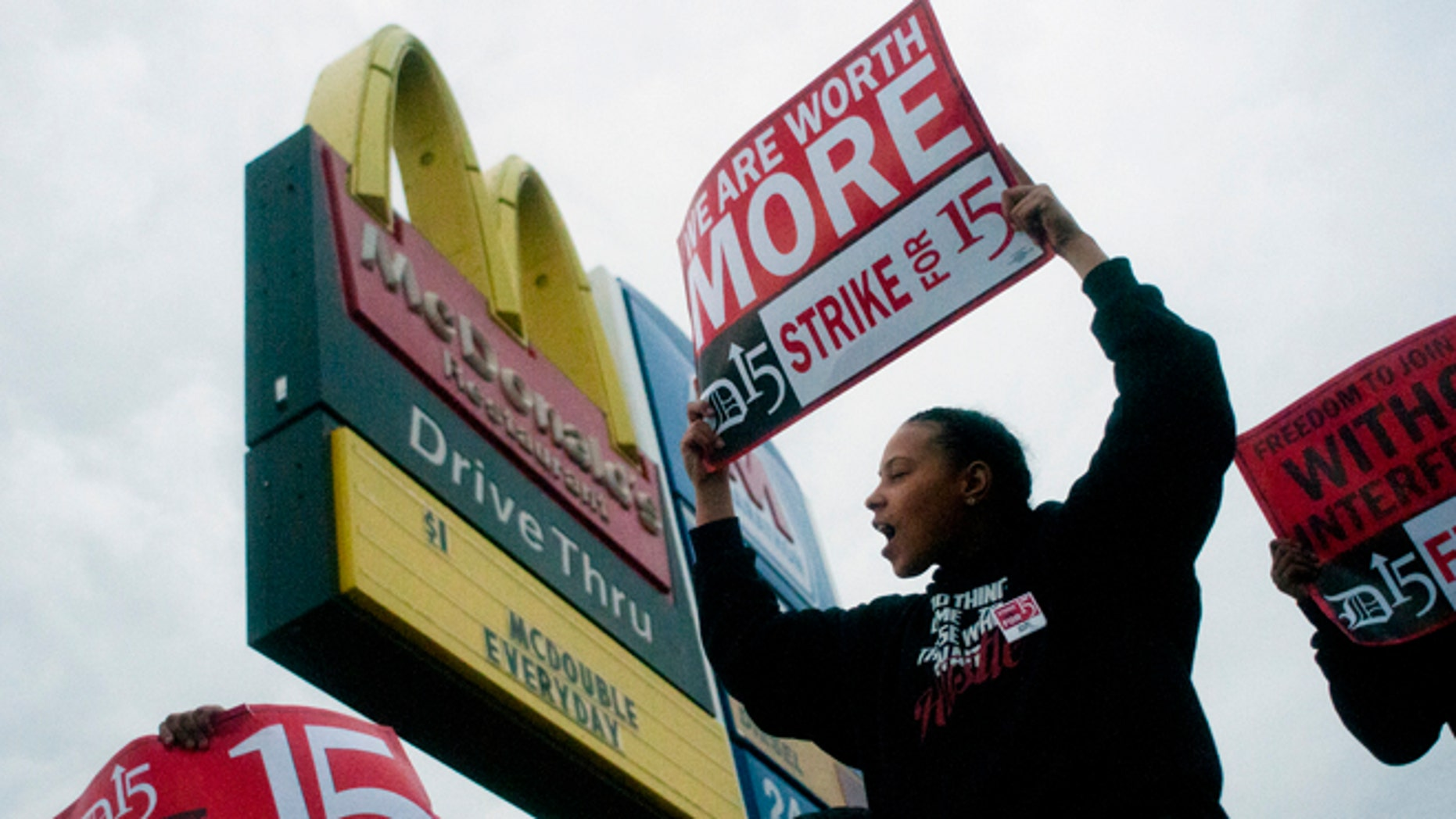 """Fast-food worker Michelle Osborn, 23, of Flint shouts out chants as she and a few dozen others strike outside of McDonald's on Wednesday, July 31, 2013 in Flint.  Some fast food restaurant workers have walked off the job in the Detroit area as part of an effort to push for higher wages. Organizers say they began the walkout at restaurants in Lincoln Park and Southfield on Tuesday night. Workers in Flint hit the street Wednesday outside a McDonald's, saying they want wages """"super-sized."""" Workers want $15 and hour, better working conditions and the right to unionize. The restaurant industry says higher wages would hurt job creation. The actions follow strikes this week in other parts of the country. (AP Photo/The Flint Journal, Jake May) LOCAL TV OUT; LOCAL INTERNET OUT"""
