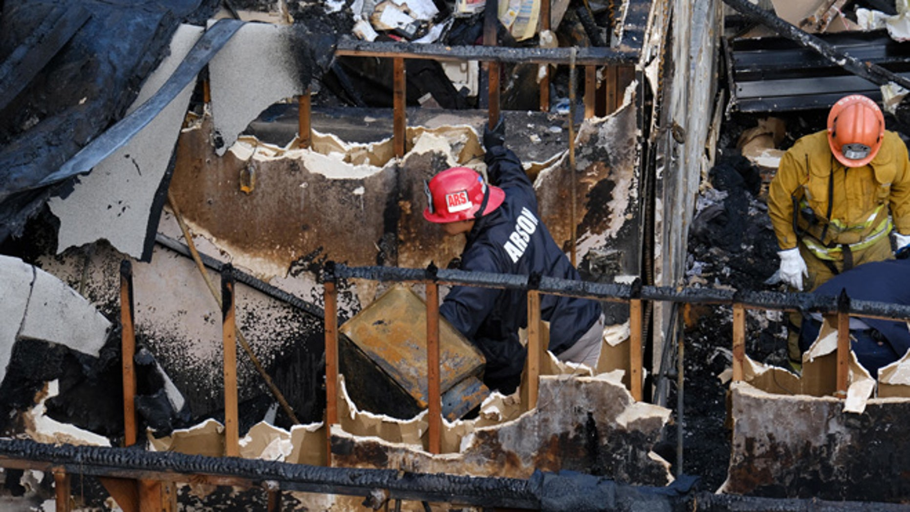 Los Angeles Fire Department arson investigators examine the burned-out ruins of an abandoned office building in the Westlake district just west of downtown Los Angeles Tuesday, June 14, 2016. Two men and two women were found Tuesday after a search using cadaver dogs, bringing the death toll to five. One person was found dead when the building burned Monday evening, June 13. Authorities believe the fire was intentionally set. (AP Photo/Richard Vogel)