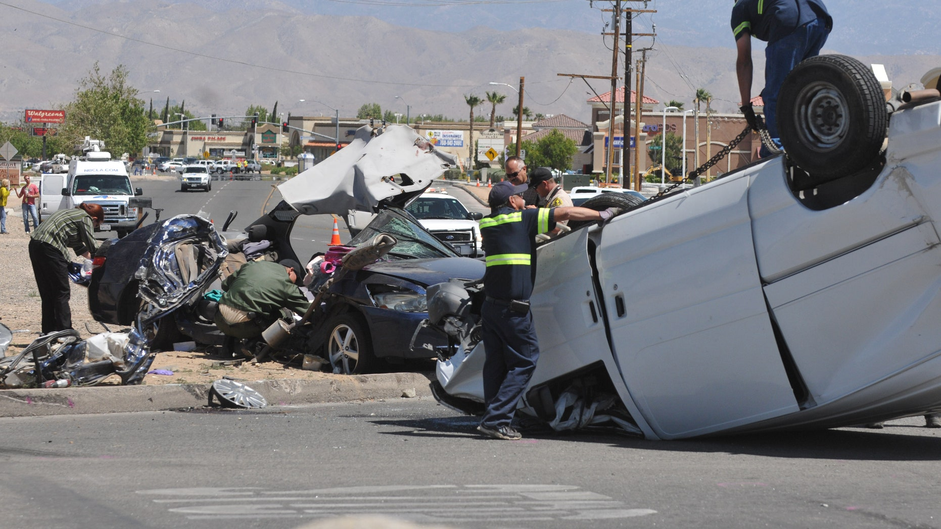 Authorities work on the scene of a fatal traffic accident in Hesperia, Calif, Sunday, May 11, 2014. A spokeswoman with the San Bernardino County Sheriff's Department says that four people are confirmed dead after a van smashed into a car that was sitting at a stop sign. (AP Photo/The Victor Valley Daily Press, David Pardo)