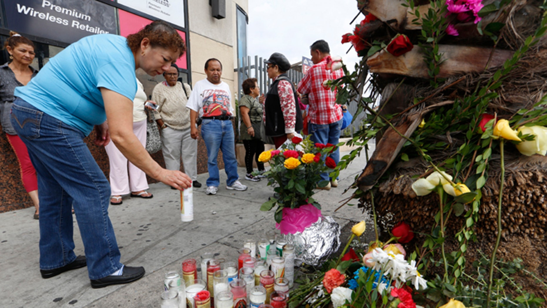 People gather at makeshift memorial at a tour bus stop in Los Angeles, Monday, Oct 24, 2016.