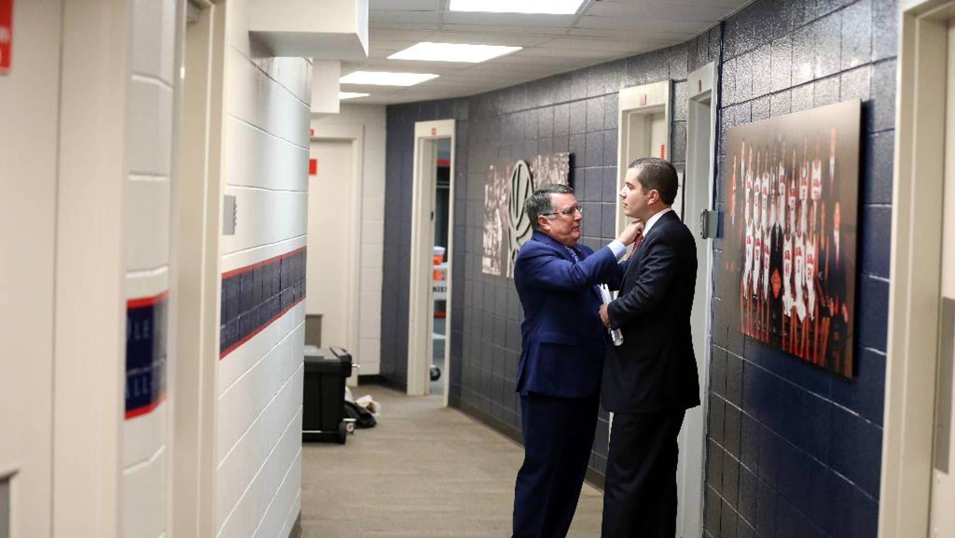 This Nov. 23, 2014, photo proved by The University of Mississippi Athletics Department shows Mississippi women's basketball coach Matt Insell, right and his father, Middle Tennessee State women's basketball coach Rick Insell, before their college basketball game in Oxford, Miss. The two coaches squared off in the first ever meeting between a father and son head coaches in NCAA Division 1 women's basketball history. (AP Photo/The University of Mississippi Athletics Department, Joshua McCoy)