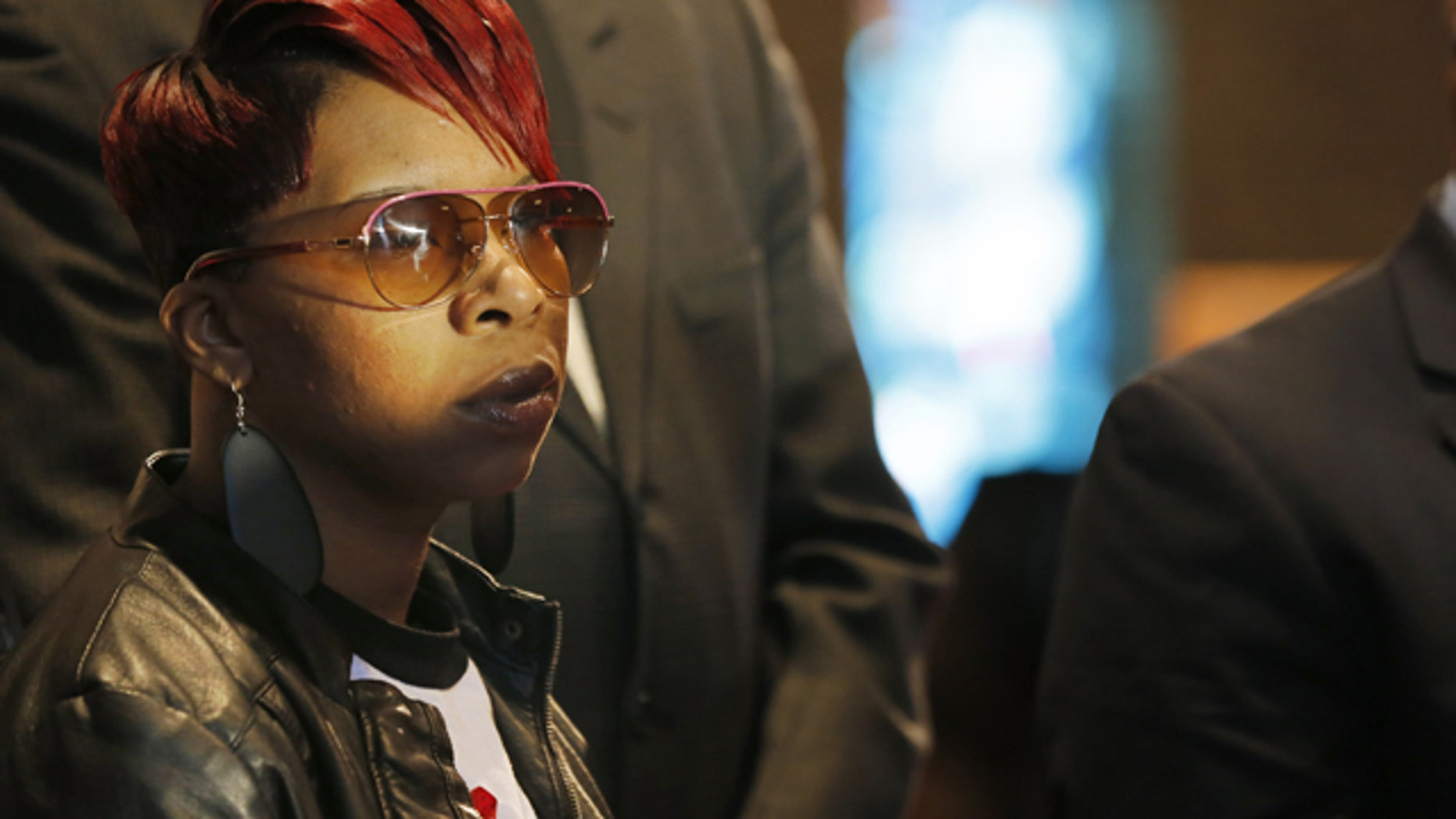 FILE - In this March 5, 2015, file photo, Lesley McSpadden, mother of Michael Brown Jr., listens to the family attorney during a news conference in Dellwood, Mo. Lawyers for the parents of Brown, the unarmed, black 18-year-old who was fatally shot by a white police officer in a St. Louis suburb, announced Wednesday, April 22, 2015, that they planned to file a civil lawsuit the following day against the city of Ferguson. (AP Photo/Charles Rex Arbogast, File)