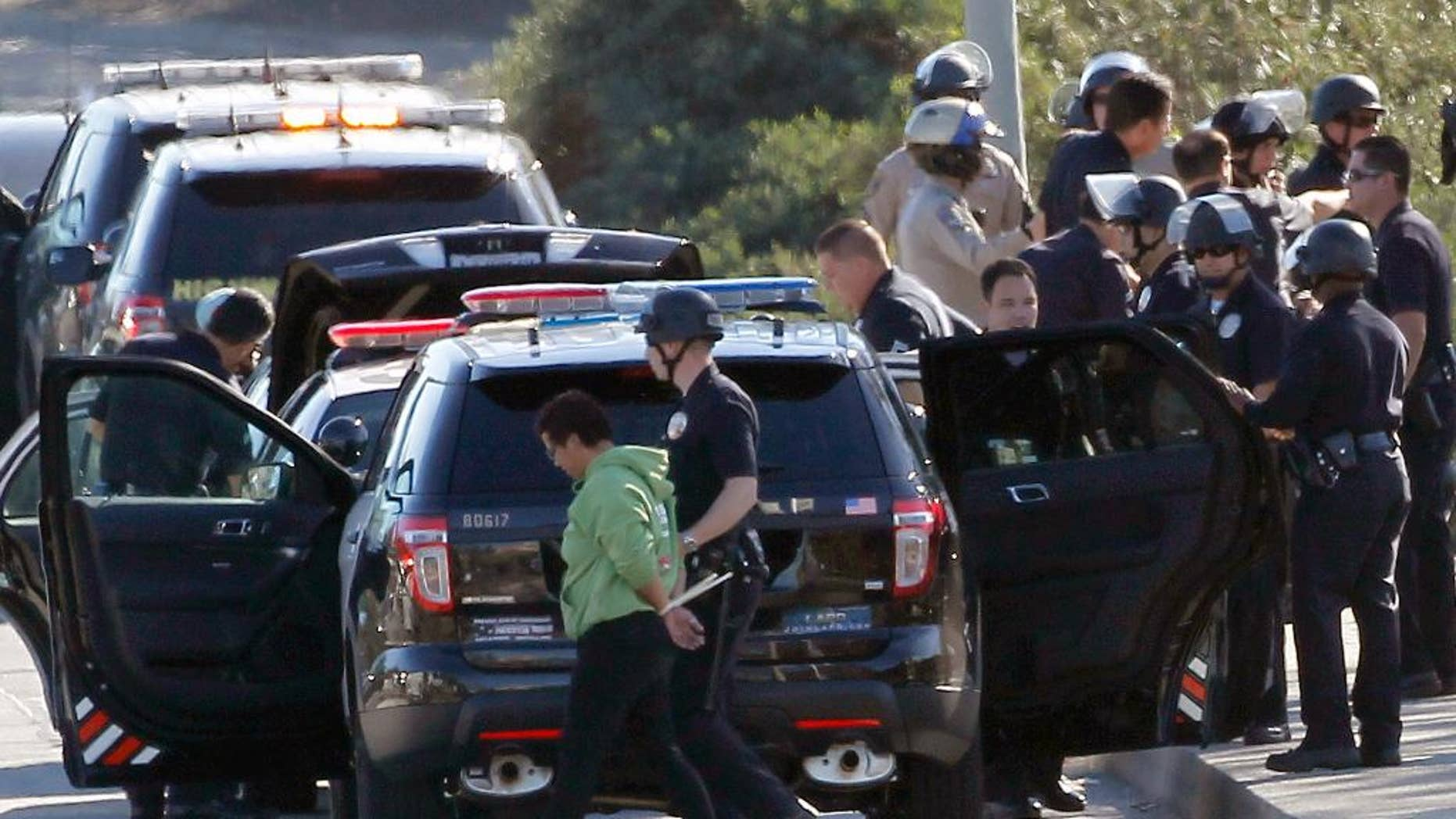 Nov. 26, 2014: A protestor is handcuffed and taken away by a police officer after the arrest of a small group of protesters who sat down in a bus lane alongside the U.S. 101.