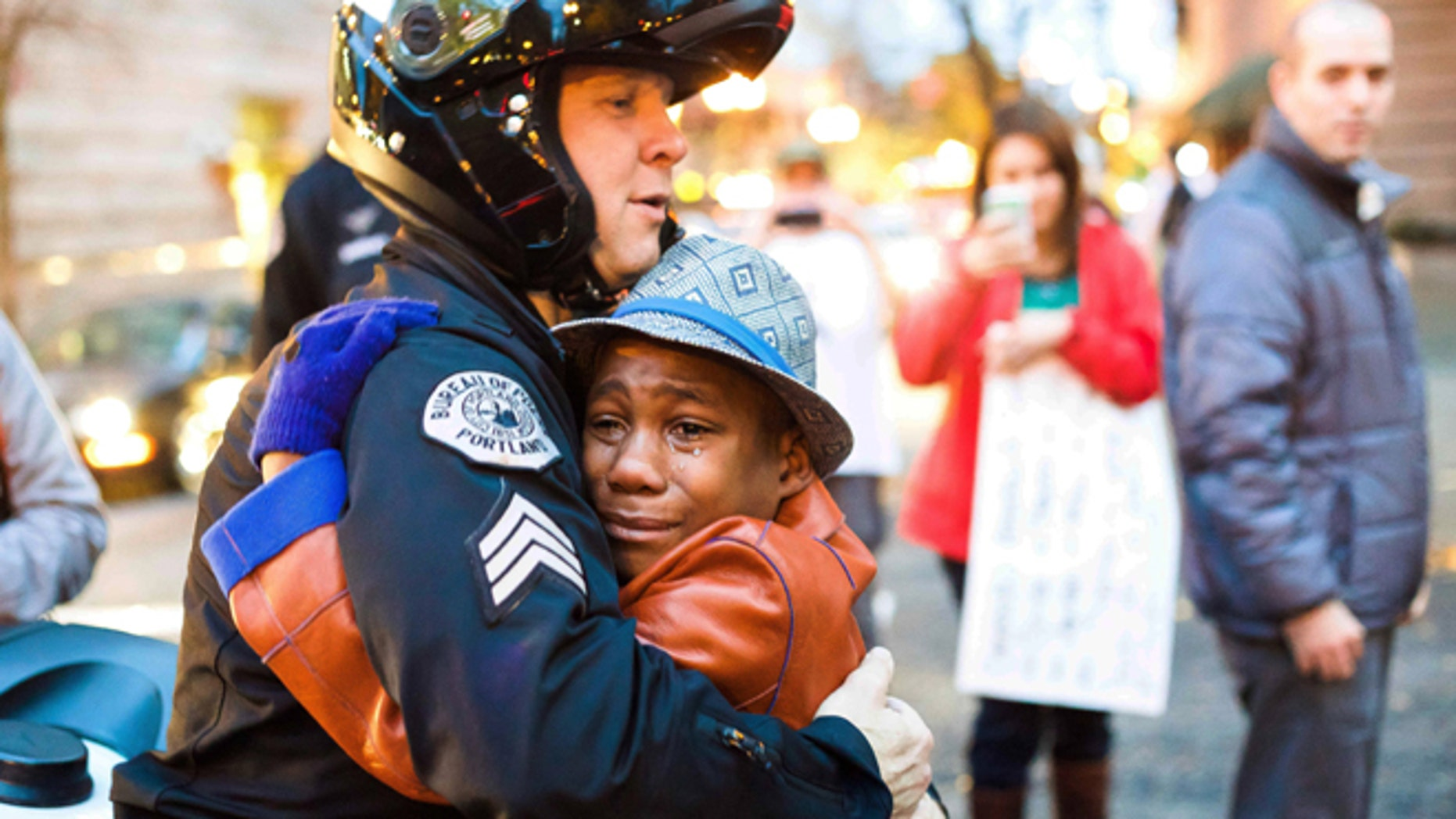 Nov. 25: Portland police Sgt. Bret Barnum, left, and Devonte Hart, 12, hug at a rally in Portland, Ore., where people had gathered in support of the protests in Ferguson, Mo.