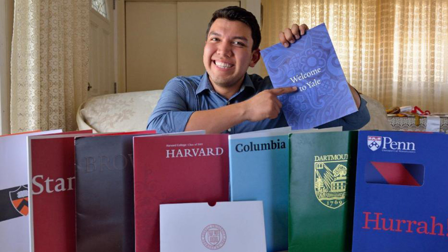 In this June 1, 2015 photo, Fernando Rojas, 17, a Fullerton High School graduate, poses for a photo in Fullerton, Calif. with literature from the eight Ivy League universities he was accepted into. He decided to attend Yale. (Leonard Ortiz/The Orange County Register via AP)