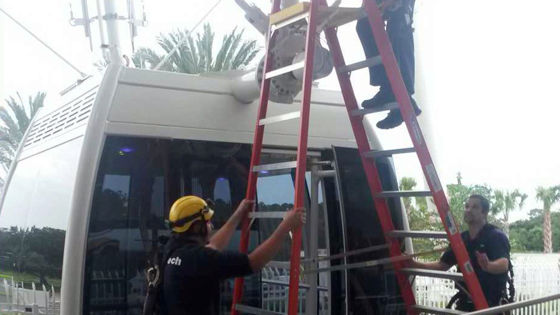In this photo provided by Orange County Fire Rescue, a technical crew with The Orlando Eye Ferris wheel work to evacuated passengers after it stopped in Orlando, Fla., Friday, July 3, 2015. Orange County Fire Rescue spokeswoman Kathleen Kennedy told The Associated Press no one was hurt and all were taken off in an operation lasting about three hours with help from firefighters. (Orange County Fire Rescue via AP)