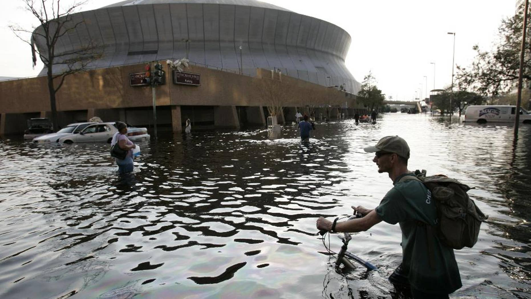 FILE - This Aug, 31, 2005 file photo shows a man pushing his bicycle through flood waters near the Superdome in  New Orleans after Hurricane Katrina left much of the city under water. A new but controversial study asks if an end is coming to the busy Atlantic hurricane seasons of recent decades. The Atlantic looks like it is entering in to a new quieter cycle of storm activity, like in the 1970s and 1980s, two prominent hurricane researchers wrote Monday in the journal Nature Geoscience.(AP Photo/Eric Gay, File)