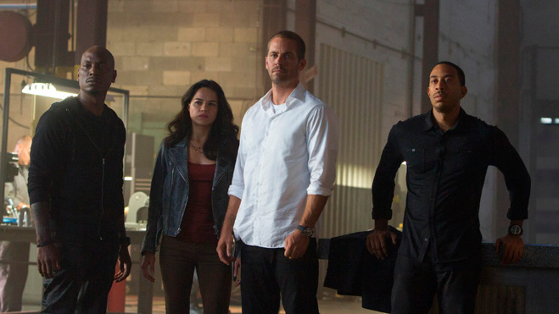 """Tyrese Gibson, Michelle Rodriguez, Paul Walker and Chris """"Ludacris"""" Bridges in the film, """"Furious 7,"""" directed by James Wan."""
