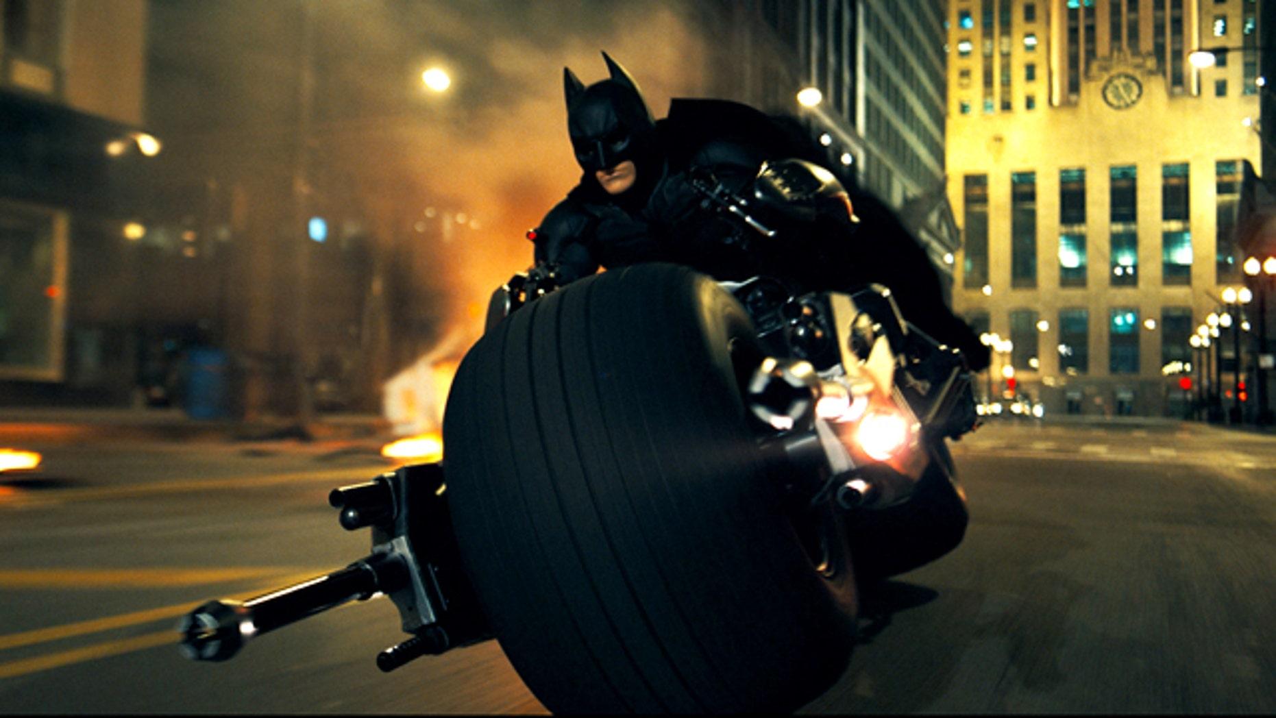 "Christian Bale rides a very custom chopper as Batman in a scene from ""The Dark Knight."""