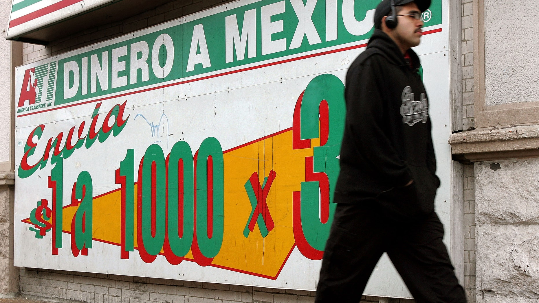A man walks past an a sign outside a a Mexican currency exchange November 29, 2005 in Chicago, Illinois. Hispanics have become a growing force in the U.S economy and politics. (Photo by Tim Boyle/Getty Images)