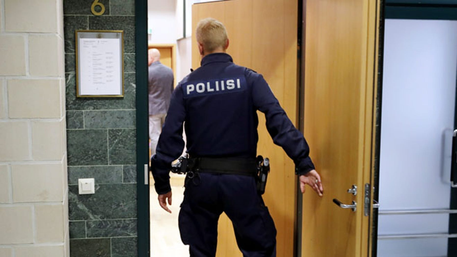 A police officer in Pirkanmaa district court in Tampere Finland, on Tuesday, July 5 2016. Finnish police have released two members of Cuba's national men's volleyball team but are holding six others on suspicion of aggravated rape, an investigator said Monday. (Kalle Parkkinen/Lehtikuva via AP)