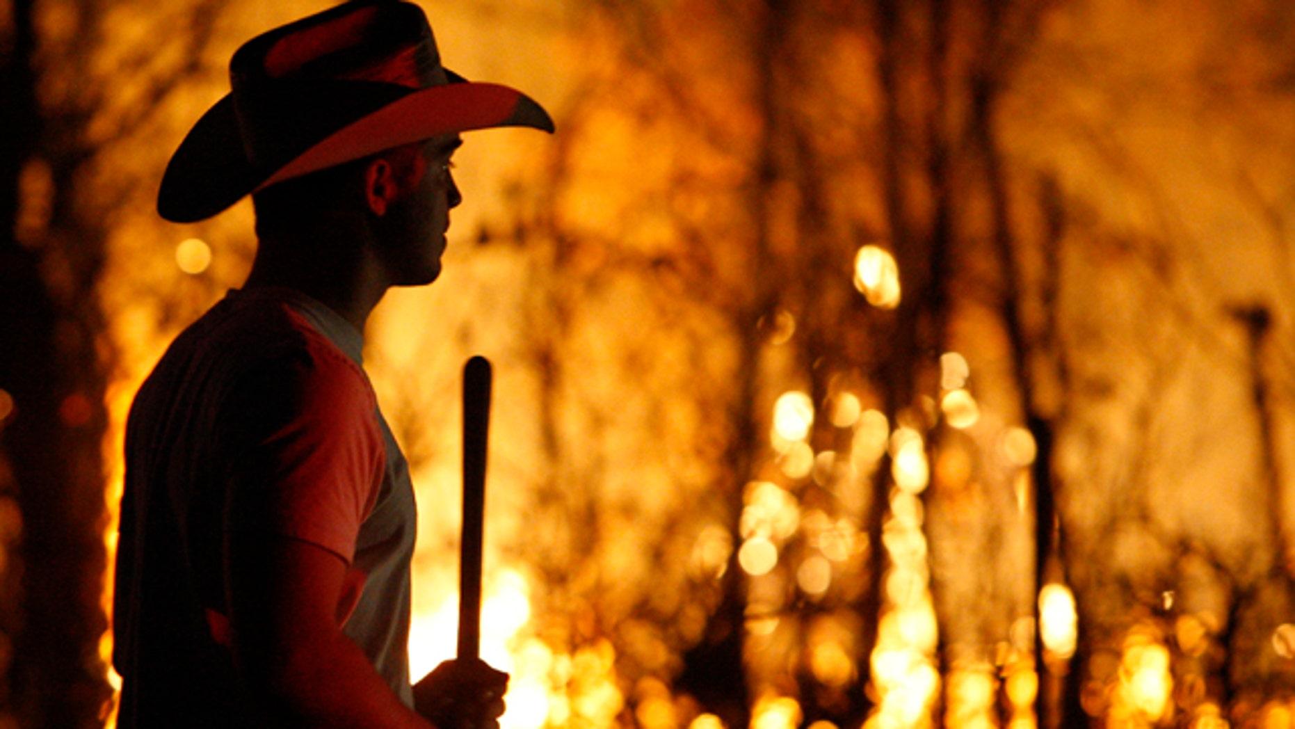 March 11, 2011: Taylor Sheets carries a shovel as he walks past a grass fire near Harrah, Okla.