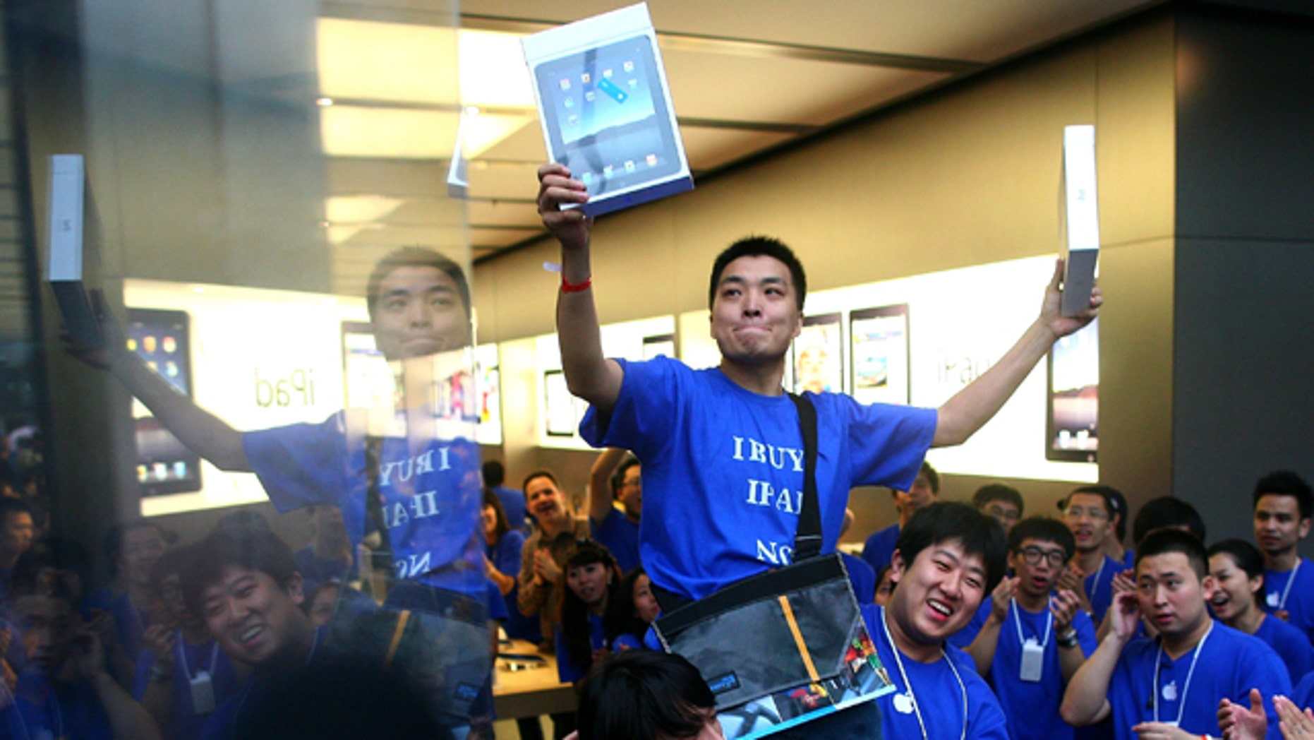 Han Ziwen holds up his iPads while being carried out by store employees at the Apple flagship store in Beijing, China, Friday, Sept. 17, 2010. Han was one of the first customers to officially buy an iPad in mainland China after lining up for more than 60 hours.