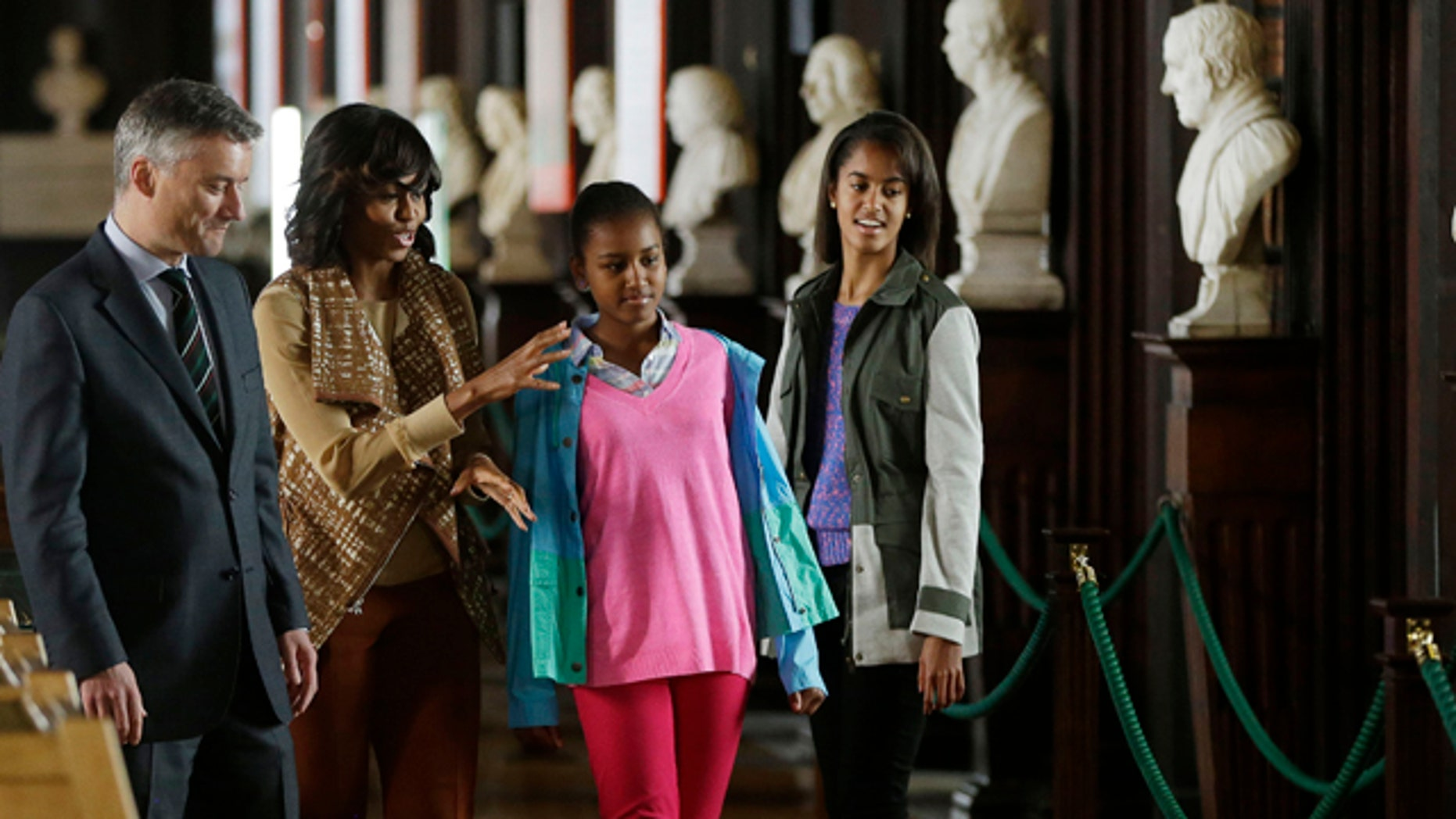 June 17, 2013: US first lady Michelle Obama, center, with her daughters Sasha, and Malia, are escorted by Patrick Prendergast, far left, President/Provost of Trinity College, during their visit to the Old Library at Trinity College, in Dublin, Ireland.