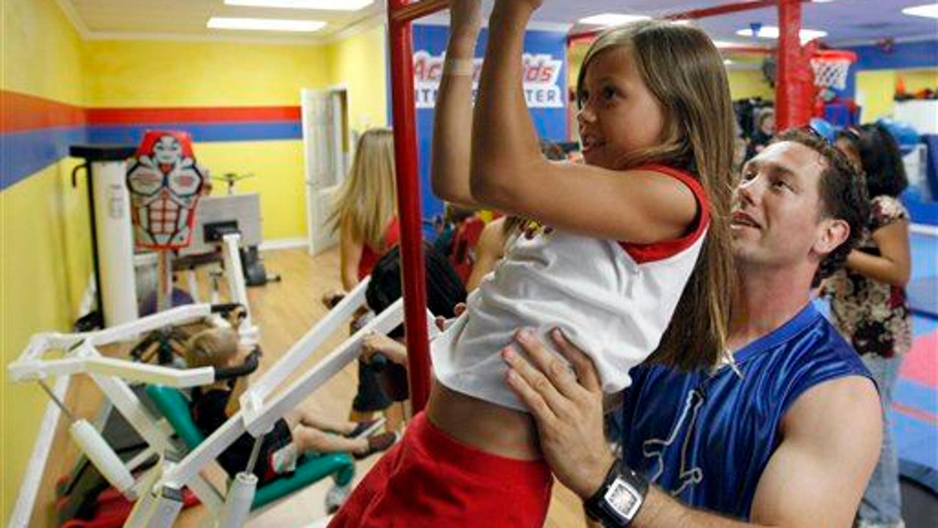 Action Fitness owner Steve Ewing, right, trains Kaela Ewing, 8, at the gym in Placentia, Calif., Tuesday, Aug. 12, 2008.