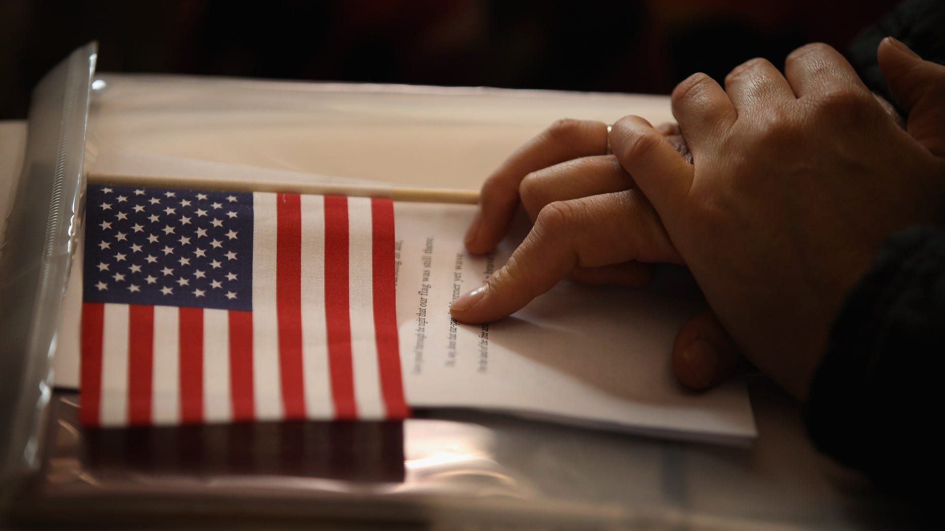 CHICAGO, IL - JULY 03: A new U.S. citizens holds and American flag along with her citizenship papers as she participates in a naturalization ceremony at the Chicago Cultural Center on July 3, 2013 in Chicago, Illinois. The ceremony, which recognized 71 new citizens from 32 countries, was one of more than 100 naturalization ceremonies held across the country and around the world to celebrate Independence Day.  (Photo by Scott Olson/Getty Images)