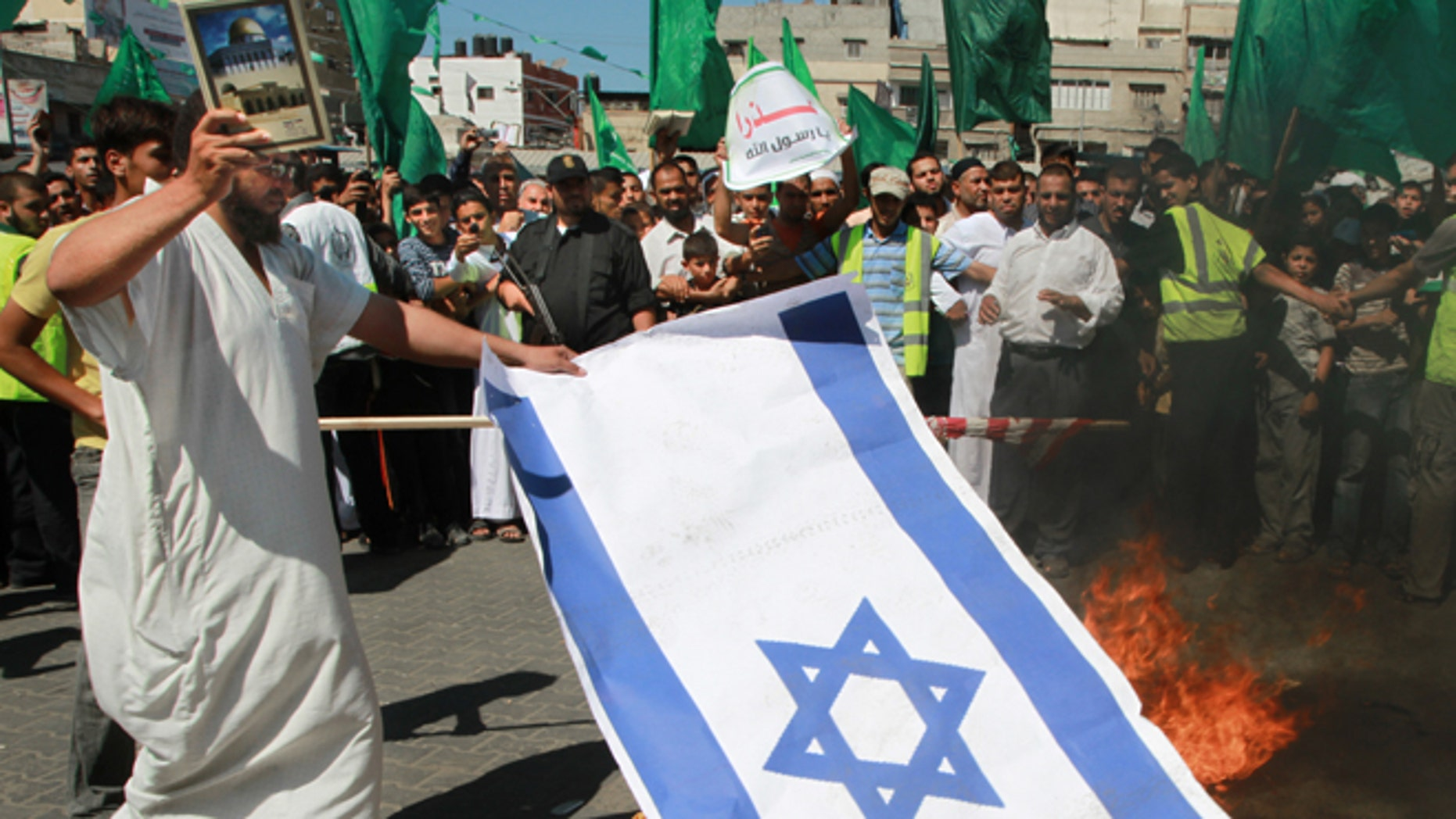 Sept. 14: A Palestinian Hamas supporter burns an Israeli flag, while holdings a Quran, Muslim's holy book, during a protest in Khan Younis, southern Gaza Strip.