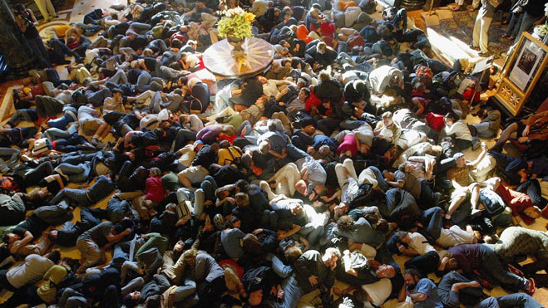 """SAN FRANCISCO - AUGUST 20:  Hundreds of people pretend to sleep as they participate in a """"flash mob"""" in the lobby of the Westin St. Francis Hotel August 20, 2003 in San Francisco, California. Flash mobs are seemingly unplanned gatherings of people arrainged by email that converge in public places for brief periods of time, perform some brief action, and then disperse.   (Photo by Justin Sullivan/Getty Images)"""