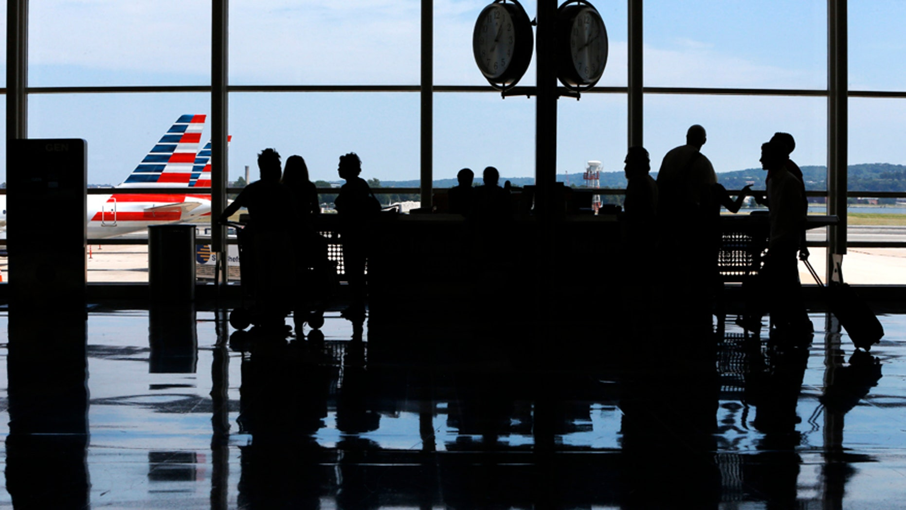 People ask questions at an information kiosk at Washington's Reagan National Airport after technical issues at a Federal Aviation Administration caused delays and cancellations on Saturday, Aug. 15, 2015.