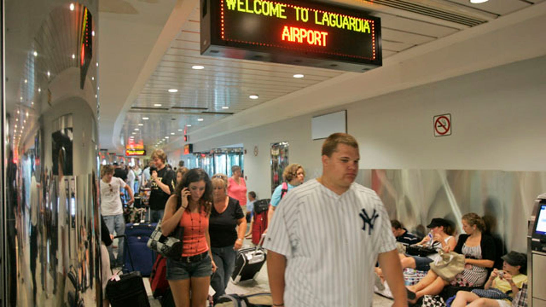 In this June 8, 2007 file photo, airline passengers navigate crowded walkways at LaGuardia  Airport in New York.