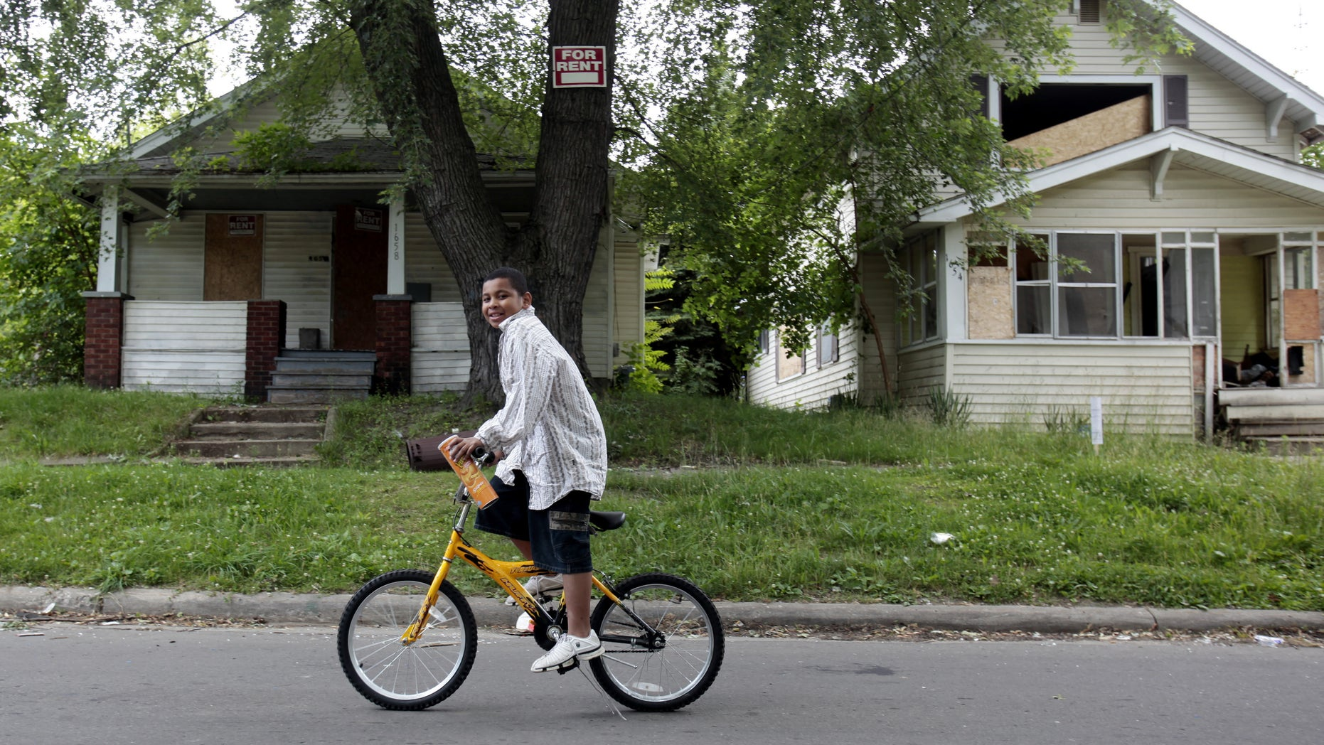 July 8, 2009 - FILE photo of a boy riding his bike past several abandoned houses in a former thriving working-class neighborhood that is now littered with blight in Flint, Michigan. A home in Flint recently went on the market for a mere $188.