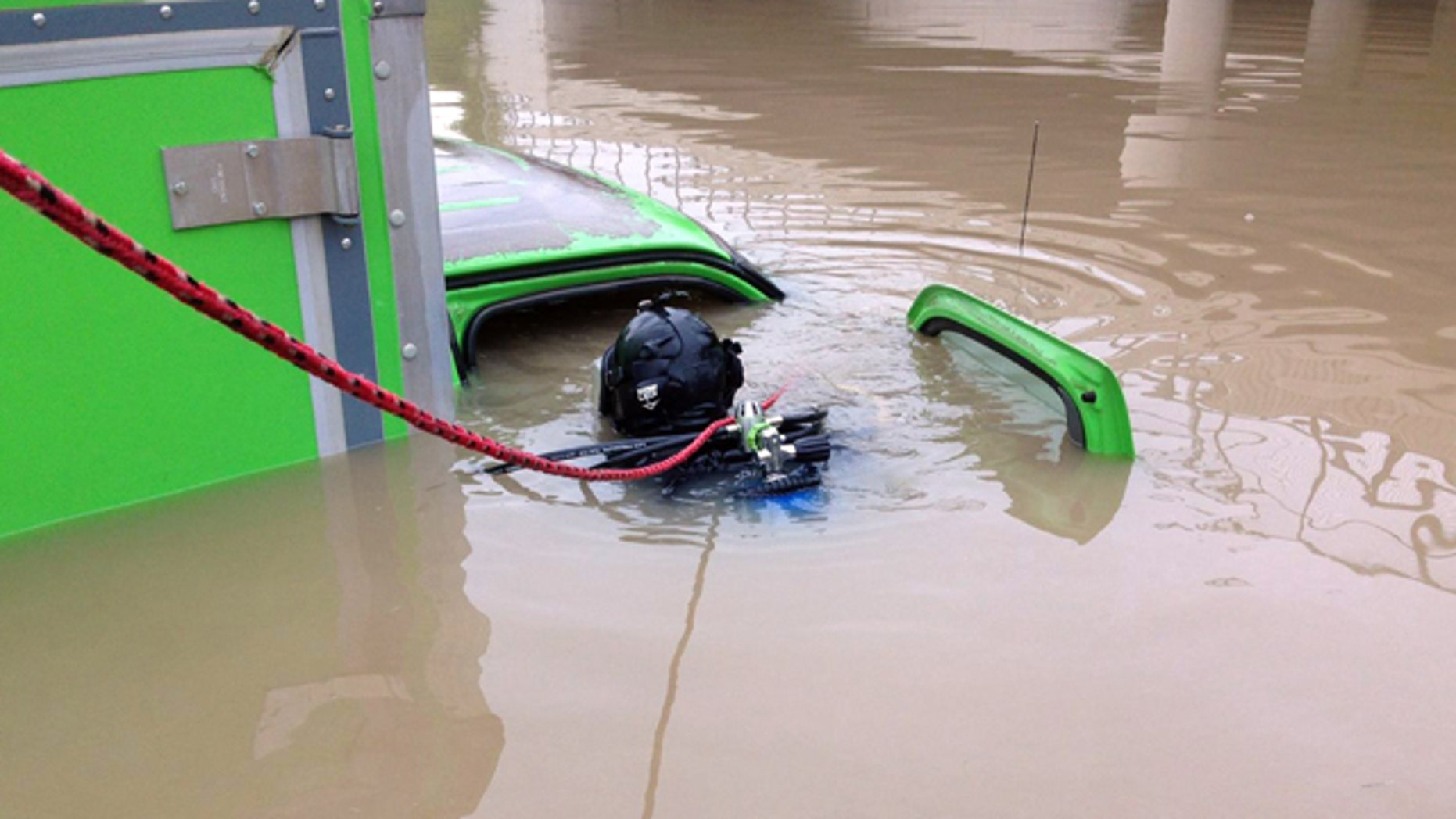 August 12, 2014: In a photo provided by the Michigan State Police, a diver with the department's Underwater Recovery Unit inspects a vehicle submerged on a Detroit area freeway a day after heavy of rain. (AP Photo/Michigan State Police)