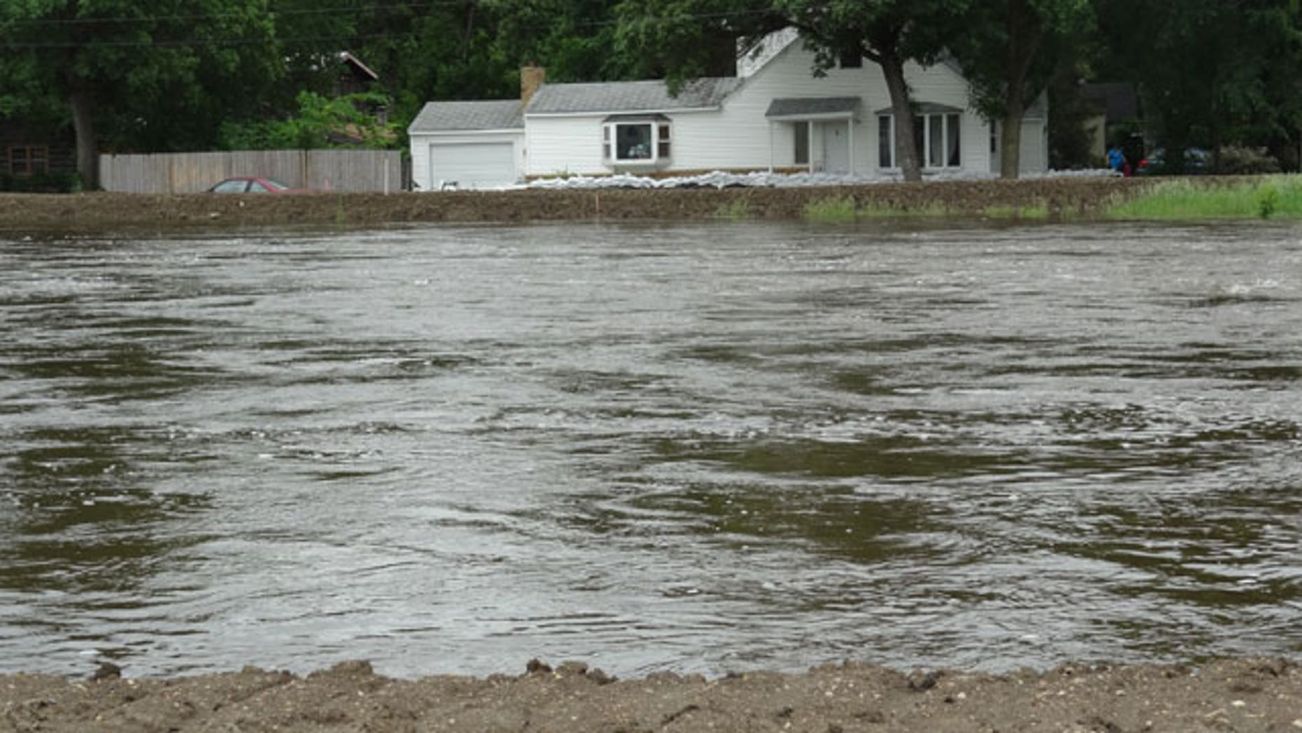 The Souris River passes near a home Tuesday, June 21, 2011, in Minot, N.D. About 11,000 Minot residents are being ordered to leave their homes even earlier than expected this week as the river gets closer to swamping the North Dakota city with the worst flooding in four decades, officials said Tuesday.
