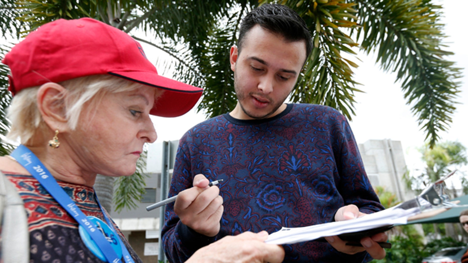 Volunteer Sandi Strickland, left, helps Roman Rodriguez, right, fill out a new voter registration form because of a change of address, as he waits in line to attend a rally for Democratic presidential candidate Hillary Clinton and former vice president Al Gore, Tuesday, Oct. 11, 2016, in Miami. A federal judge has given Democrats a partial victory in the presidential battleground of Florida, extending the state's voter registration deadline one day and agreeing to consider a longer extension in the wake of Hurricane Matthew. (AP Photo/Wilfredo Lee)