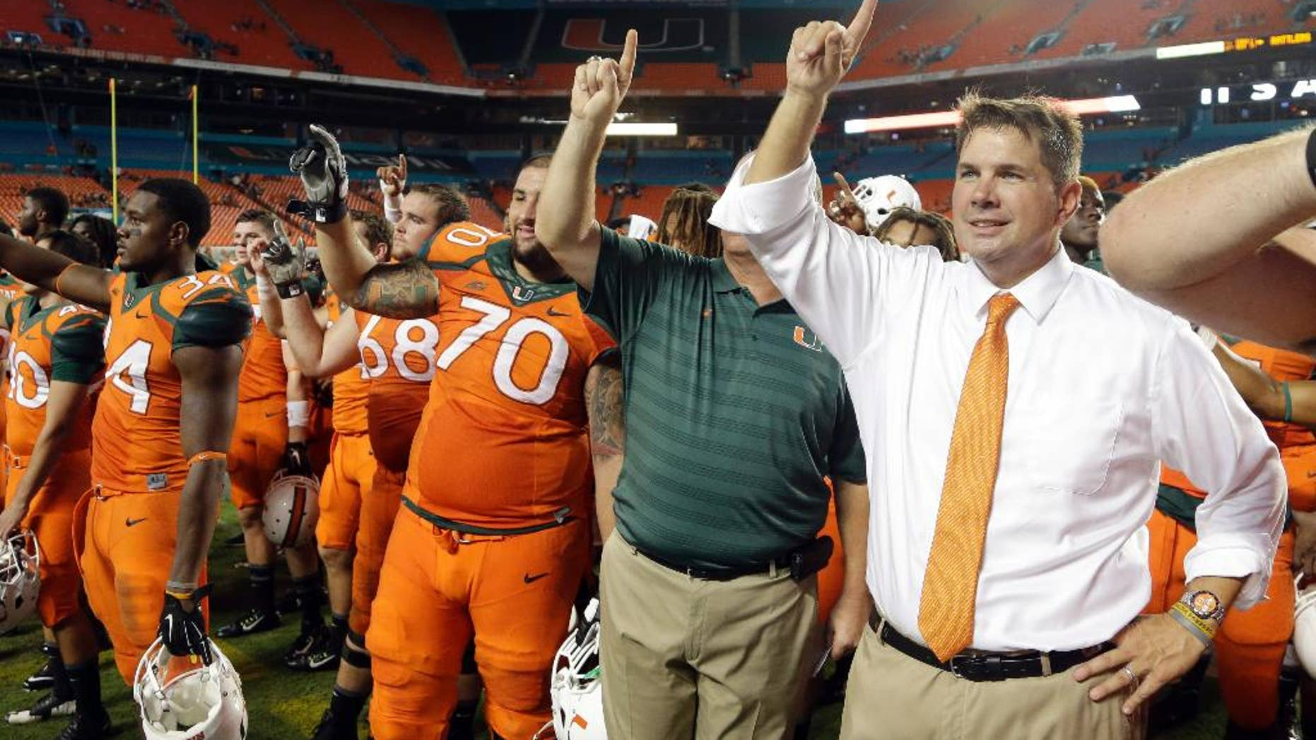 Miami head coach Al Golden, right, sings the alma mater with the team after Miami defeated Florida A&M 41-7 in an NCAA football game, Saturday, Sept. 6, 2014, in Miami Gardens, Fla. (AP Photo/Lynne Sladky)