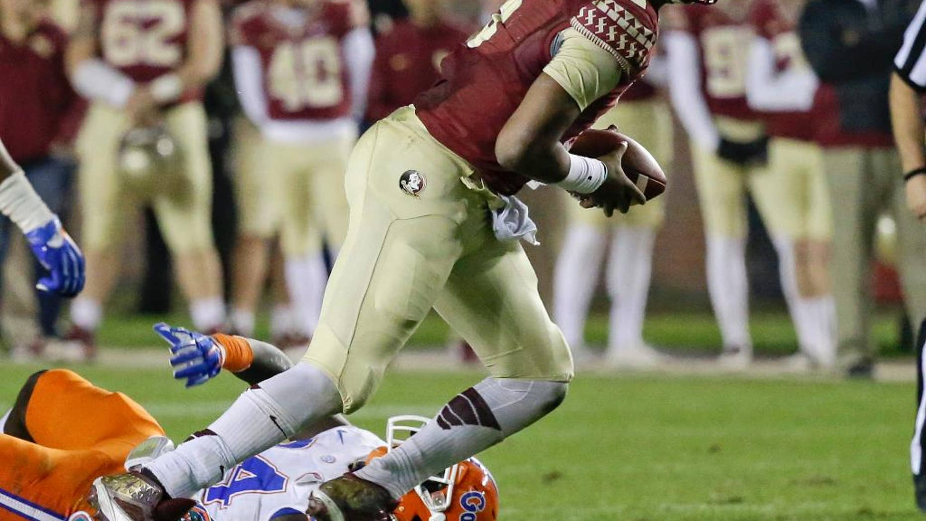 Florida State quarterback Jameis Winston scrambles out of the pocket as he is pressured by Florida defensive back Brian Poole during the second half of an NCAA college football game in Tallahassee, Fla., Saturday, Nov. 29, 2014. Florida State won 24-19. (AP Photo/John Raoux)