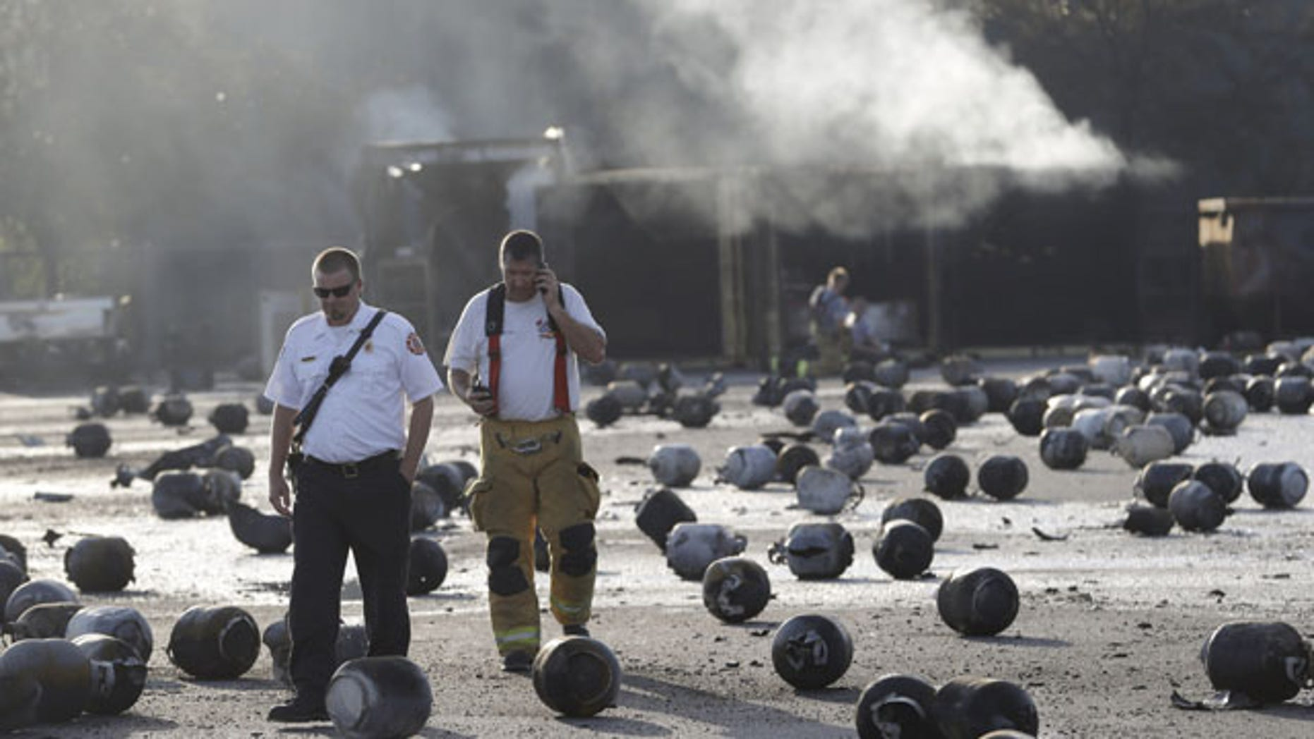 July 30, 2013: Firefighters walk through an area of exploded propane cylinders in the aftermath of an explosion and fire at a propane gas company in Tavares, Fla. (AP Photo)