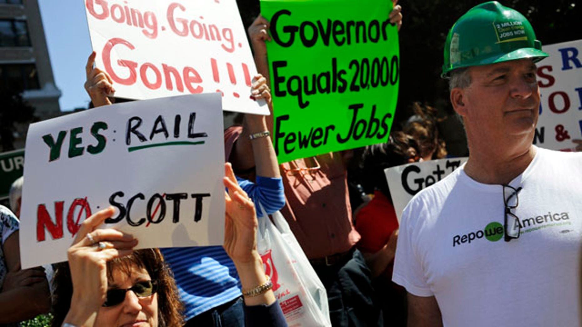 Feb. 21: Erik Arens, right, stands beside Farah Stokes as they participate in a rally to support a high-speed rail at City Hall Plaza in downtown Tampa, Fla. Gov. Rick Scott rejected $2.4 billion in federal funding for the bullet train project.