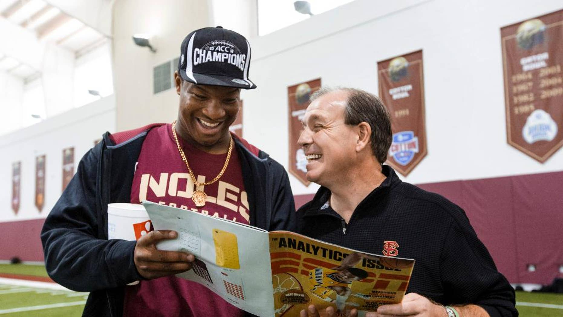 Florida State Jimbo Fisher, right, looks at a magazine with quarterback Jameis Winston during pro day at Florida State on Tuesday, March 18, 2014, in Tallahassee, Fla. Winston did not participate in pro day, but came by to visit Fisher after the event. (AP Photo/Colin Hackley)