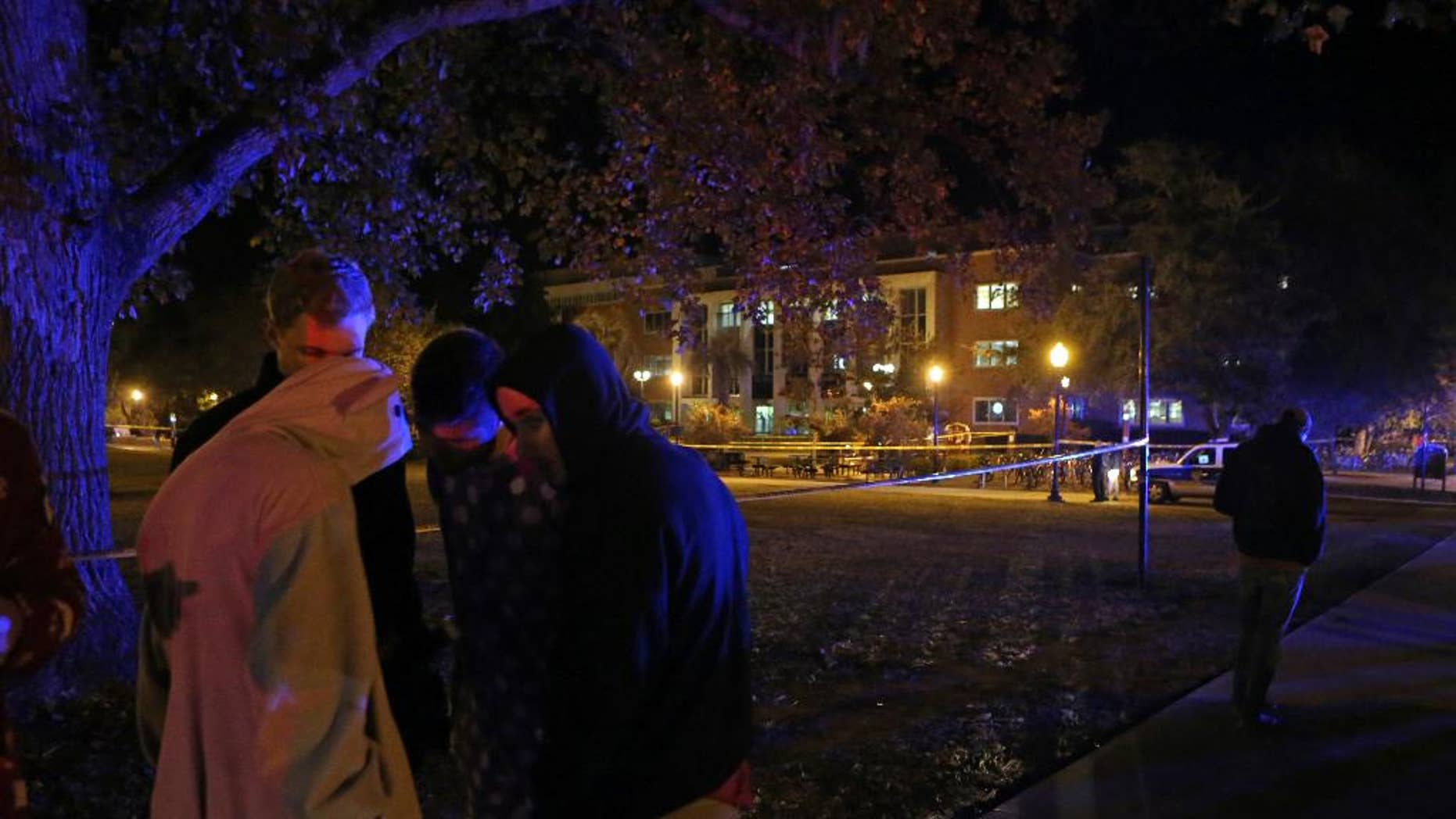 A group of students call their friends still locked down in Strozier Library, background, after a shooting on Thursday, Nov. 20, 2014, in Tallahassee, Fla. (AP Photo/Steve Cannon)