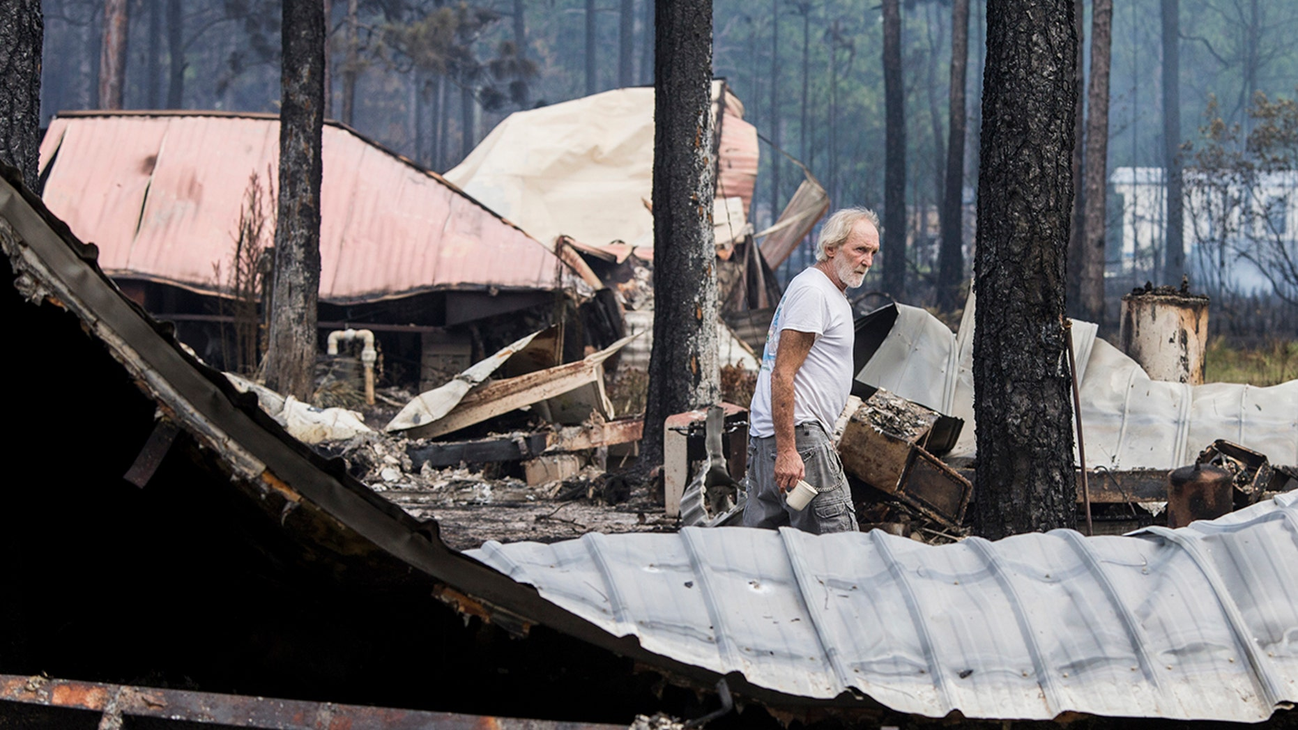 Earl Moss looks over his burned home, foreground, after wildfires swept through his neighborhood on Ridge Road in Eastpoint, Fla., Monday, June 25, 2018. (AP Photo/Mark Wallheiser)